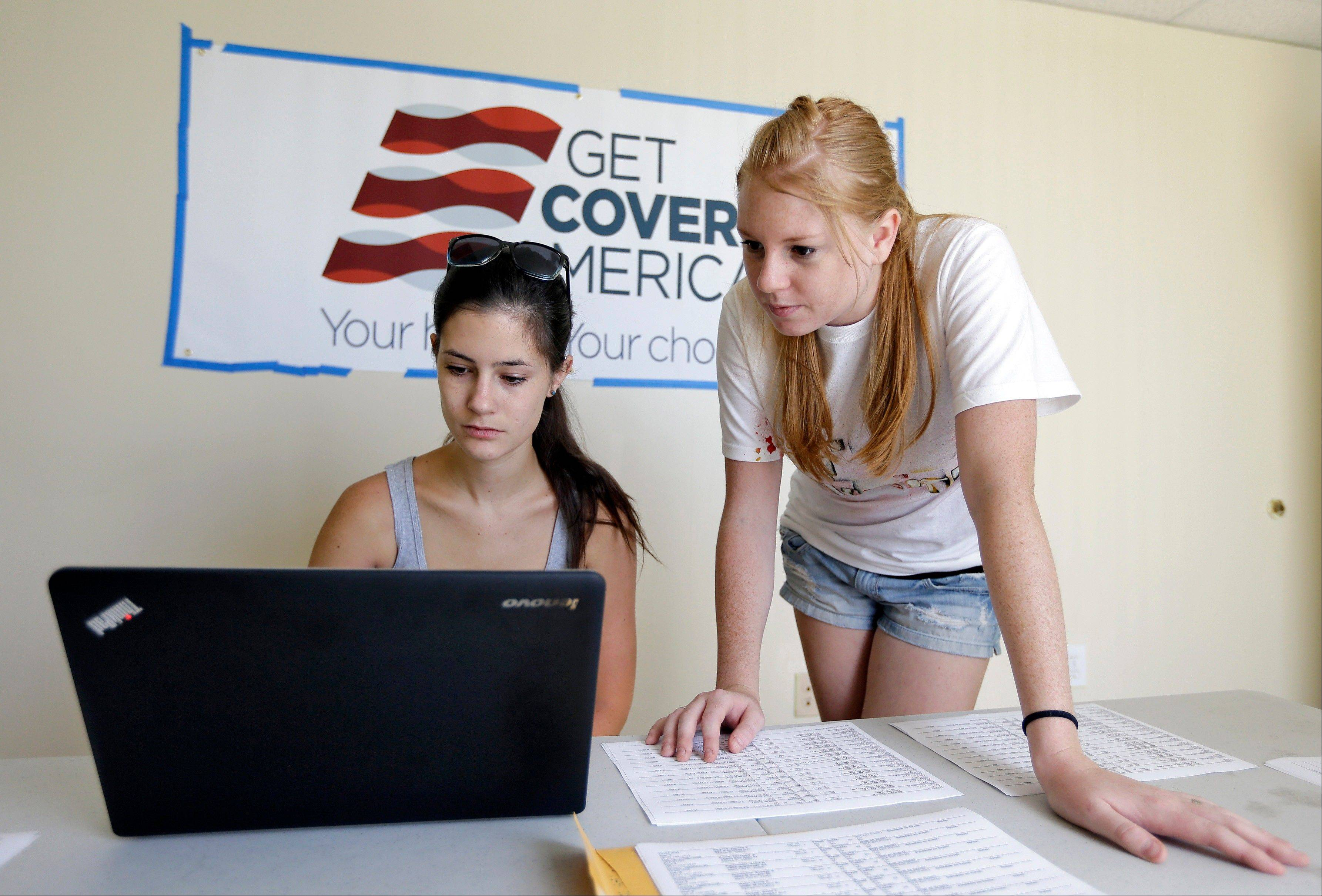 Ashley Hentze, left, of Lakeland, Fla., gets help signing up for health care from Kristen Nash, a volunteer with Enroll America, a private, non-profit organization running a grassroots campaign to encourage people to sign up for health care, Tuesday, Oct. 1, in Tampa. After months of build up, Florida residents can start shopping for health insurance on government-run online marketplaces as the key component of President Barack Obama's signature health care law.