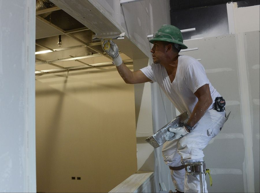 Joel Espitia covers drywall joints Friday as construction continues at the new GiGi's Playhouse National Achievement Center.