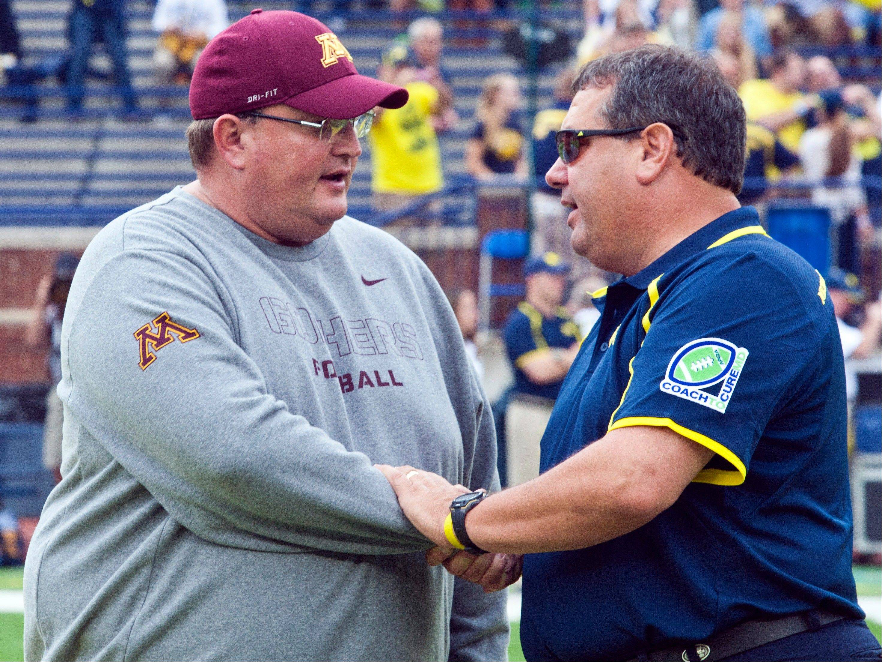 Minnesota defensive coordinator and acting head coach Tracy Claeys, left, shakes hands with Michigan head coach Brady Hoke before an NCAA college football game, Saturday, Oct. 5, 2013, in Ann Arbor, Mich. Minnesota coach Jerry Kill has suffered another seizure and did not make the trip.