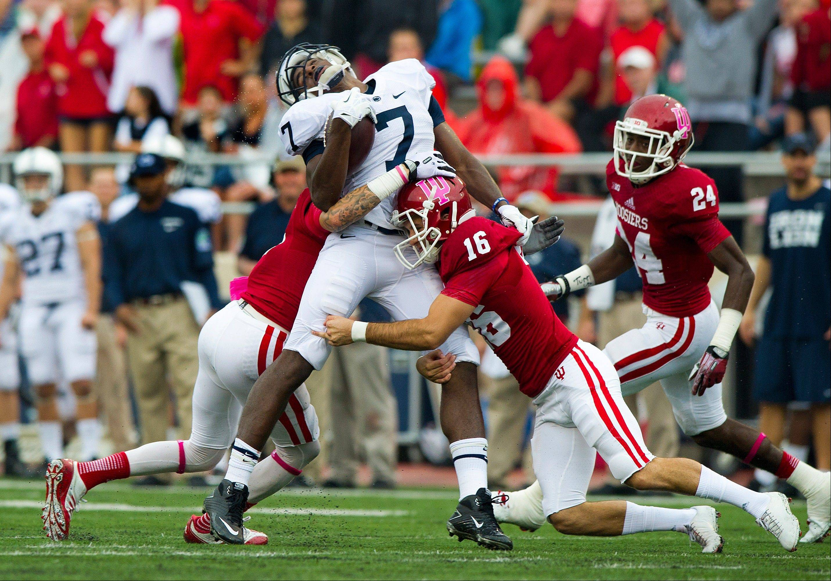 Penn State's Geno Lewis (7) is hit by Indiana's Rashard Fant (16) and Tim Bennett (24) after a pass reception during the first half of an NCAA college football game, Saturday, Oct. 5, 2013, in Bloomington, Ind.