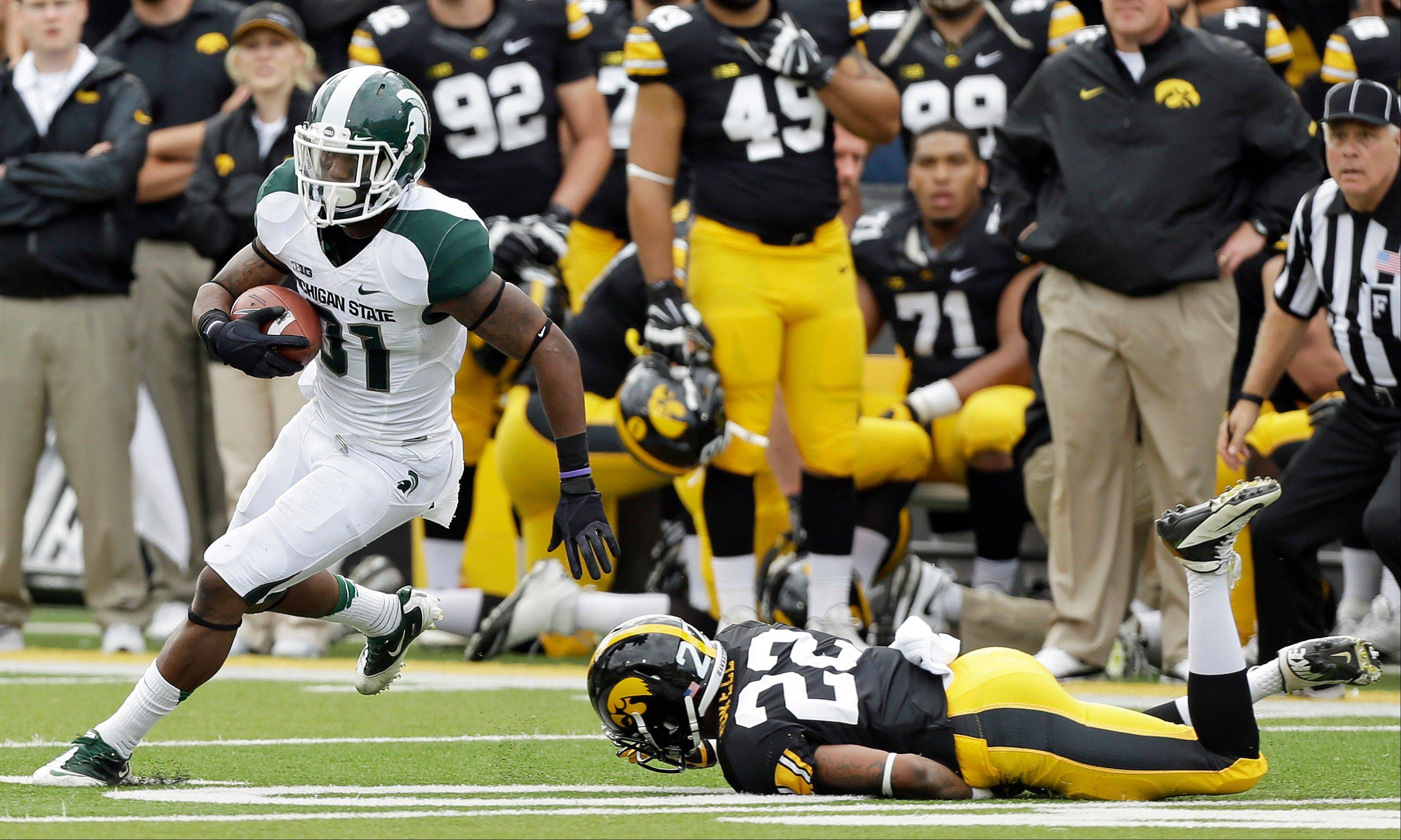 Michigan State cornerback Darqueze Dennard, left, runs past Iowa wide receiver Damond Powell (22) after intercepting a pass during the second half of an NCAA college football game, Saturday, Oct. 5, 2013, in Iowa City, Iowa. Michigan State won 26-14.