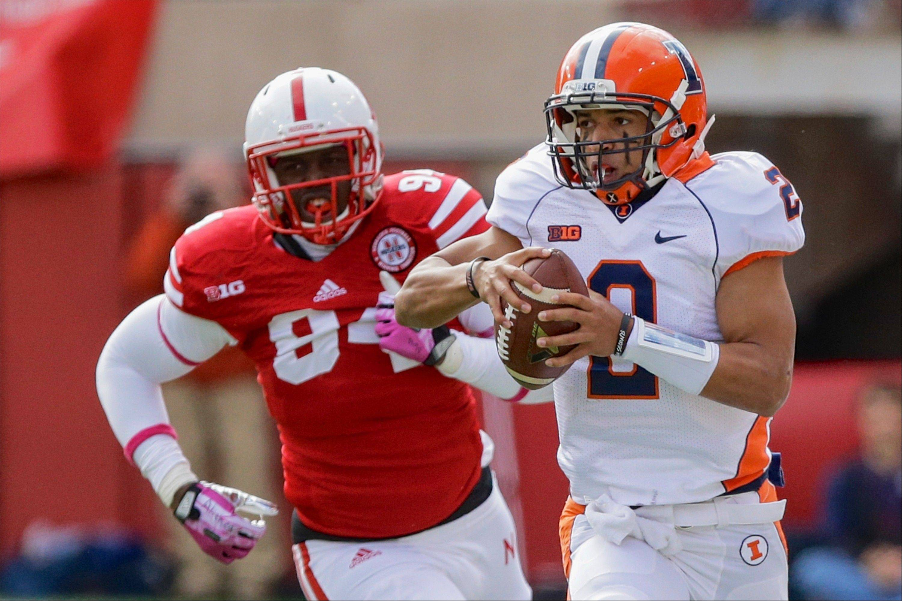 Illinois quarterback Nathan Scheelhaase (2) is pursued by Nebraska defensive end Avery Moss (94) in the first half in Lincoln, Neb., Saturday.
