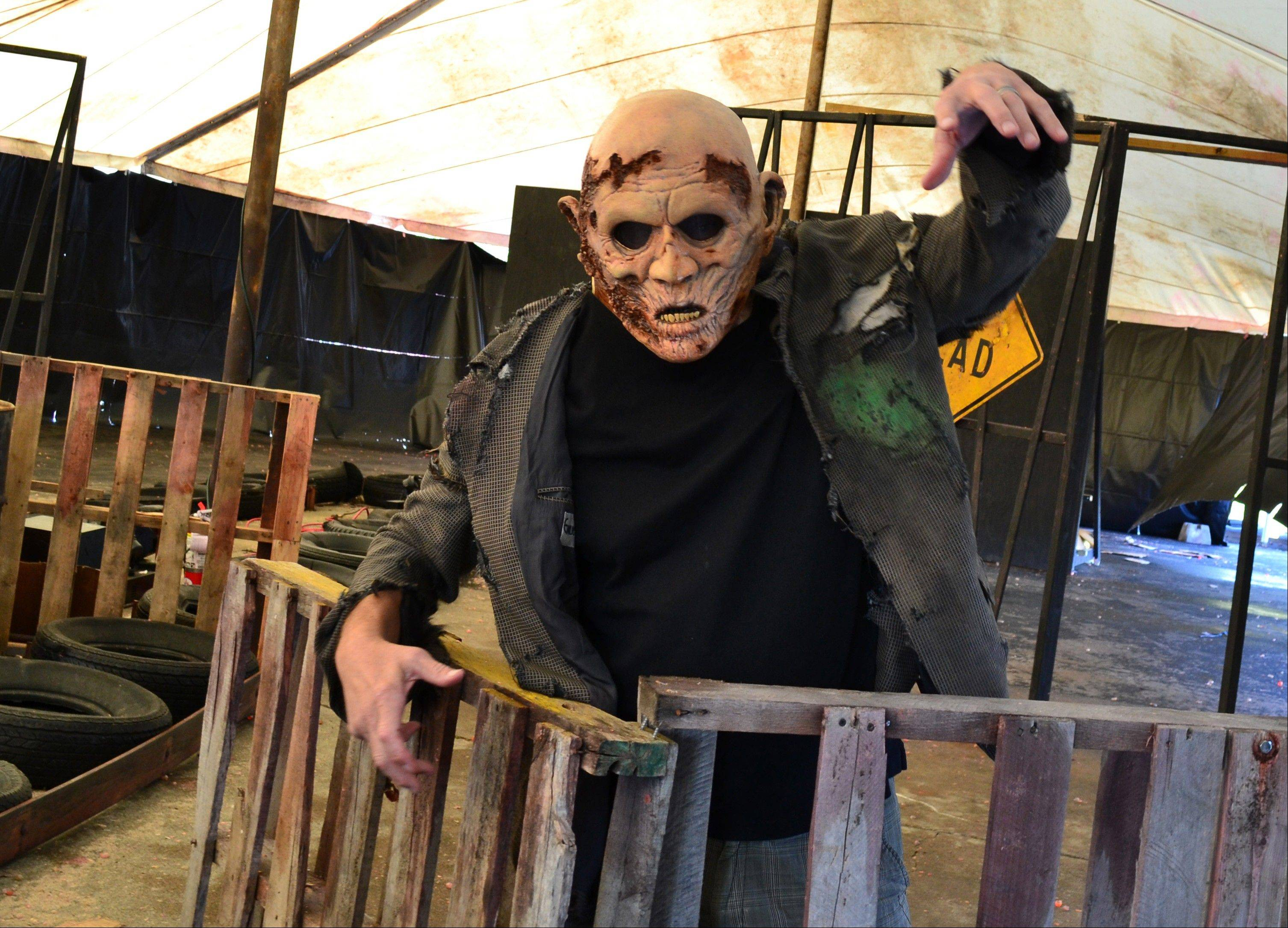 At Saint Lucifer's Haunted Asylum in Flint, Mich., a zombie awaits his fate from paintball-shooting visitors. The shoot-the-zombie game is part of a trend in which Halloween attractions are becoming more interactive.