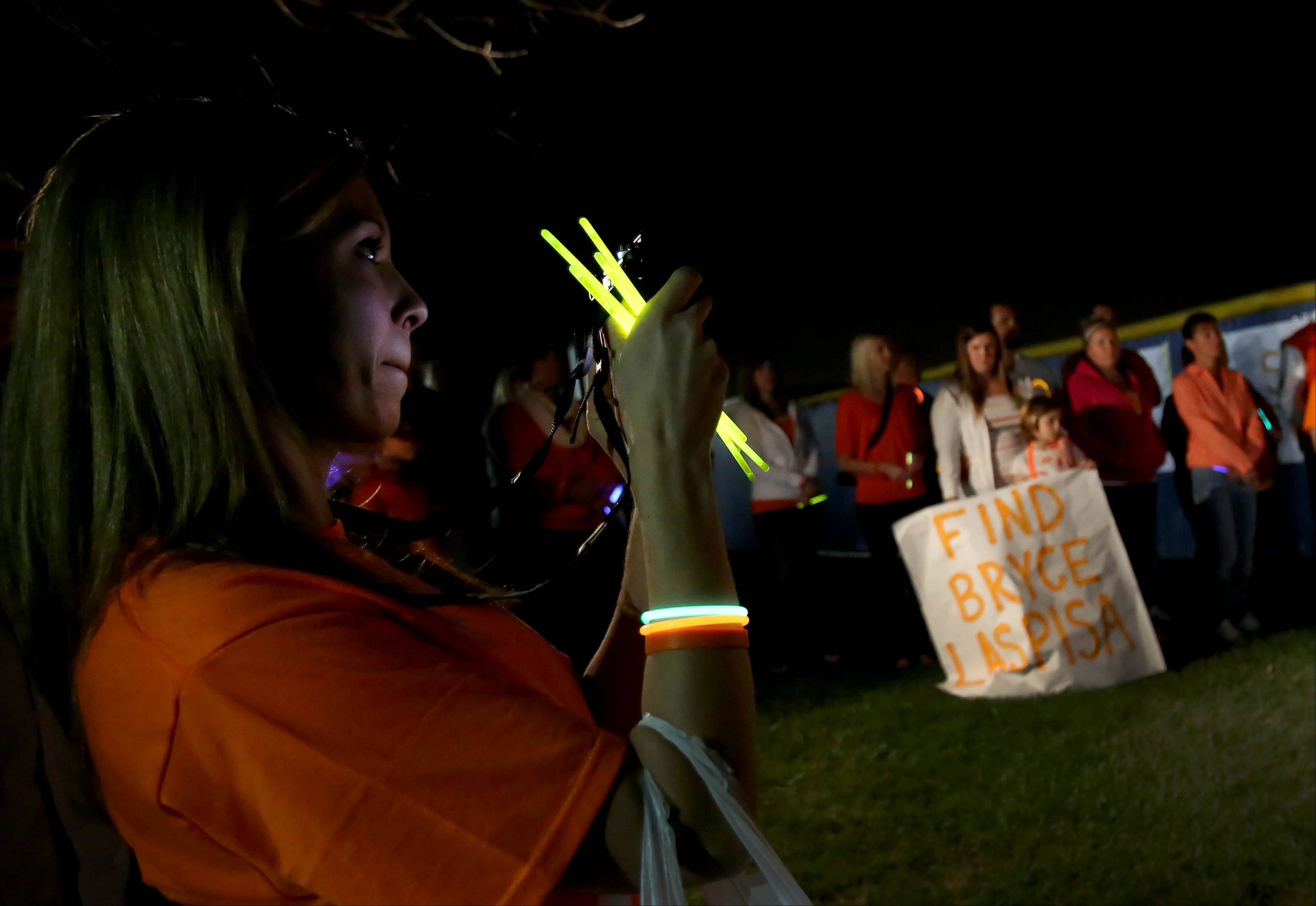 Emily Barenbrugge, who used to babysit for Bryce Laspisa and helped to organize the vigil, holds a glow stick during a vigil for the missing Naperville Central High School graduate at Frontier Park in Naperville on Monday. Participants held glow sticks or cell phone lights and wore white or orange to �light the way home� for Laspisa, a 19-year-old who went missing Aug. 30 in California. This is one of three vigils his parents are organizing to honor the teen who has been missing for a month.