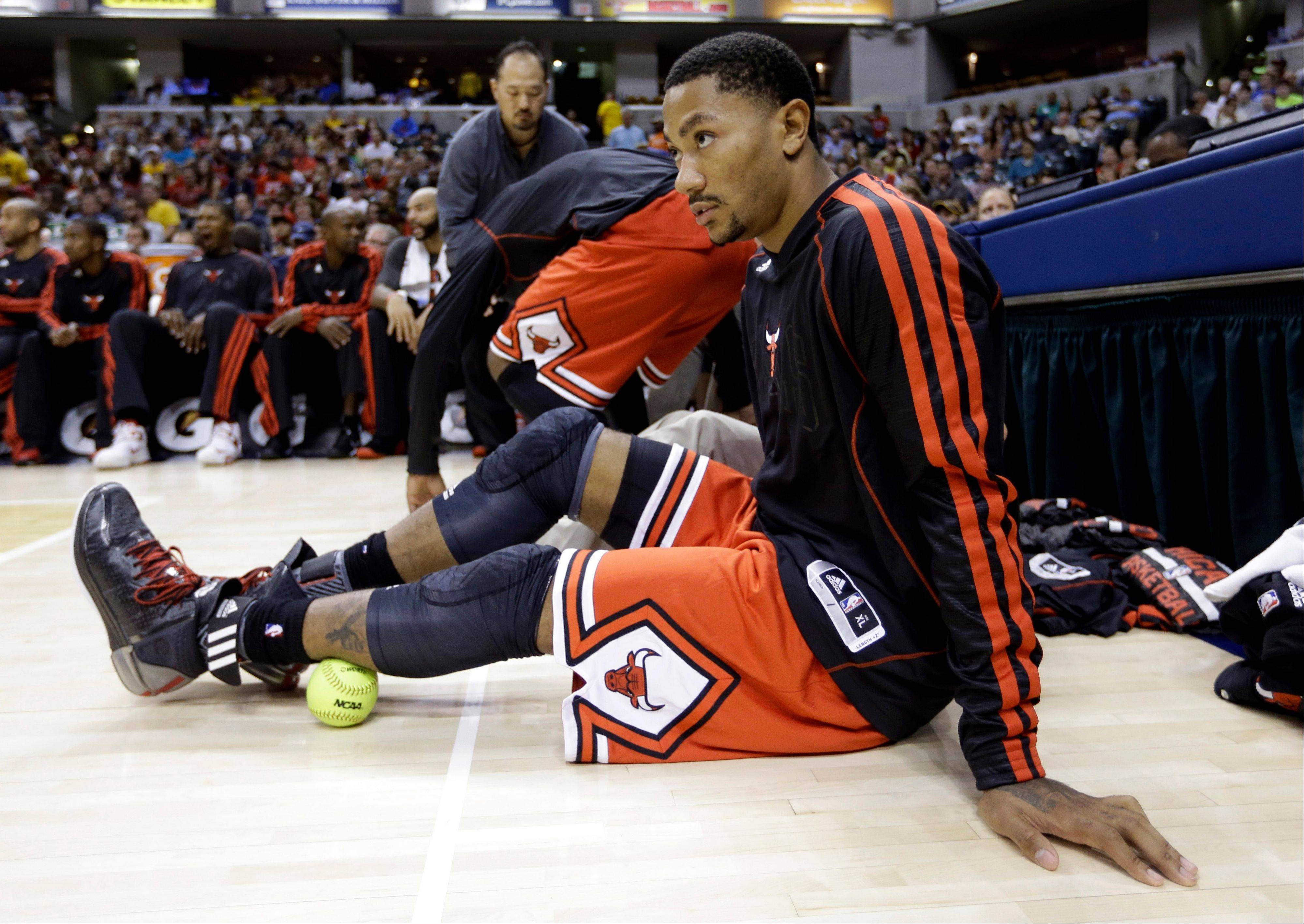 Bulls guard Derrick Rose uses a softball to loosen up a muscle as he sits in front of the bench in the first half Saturday night.