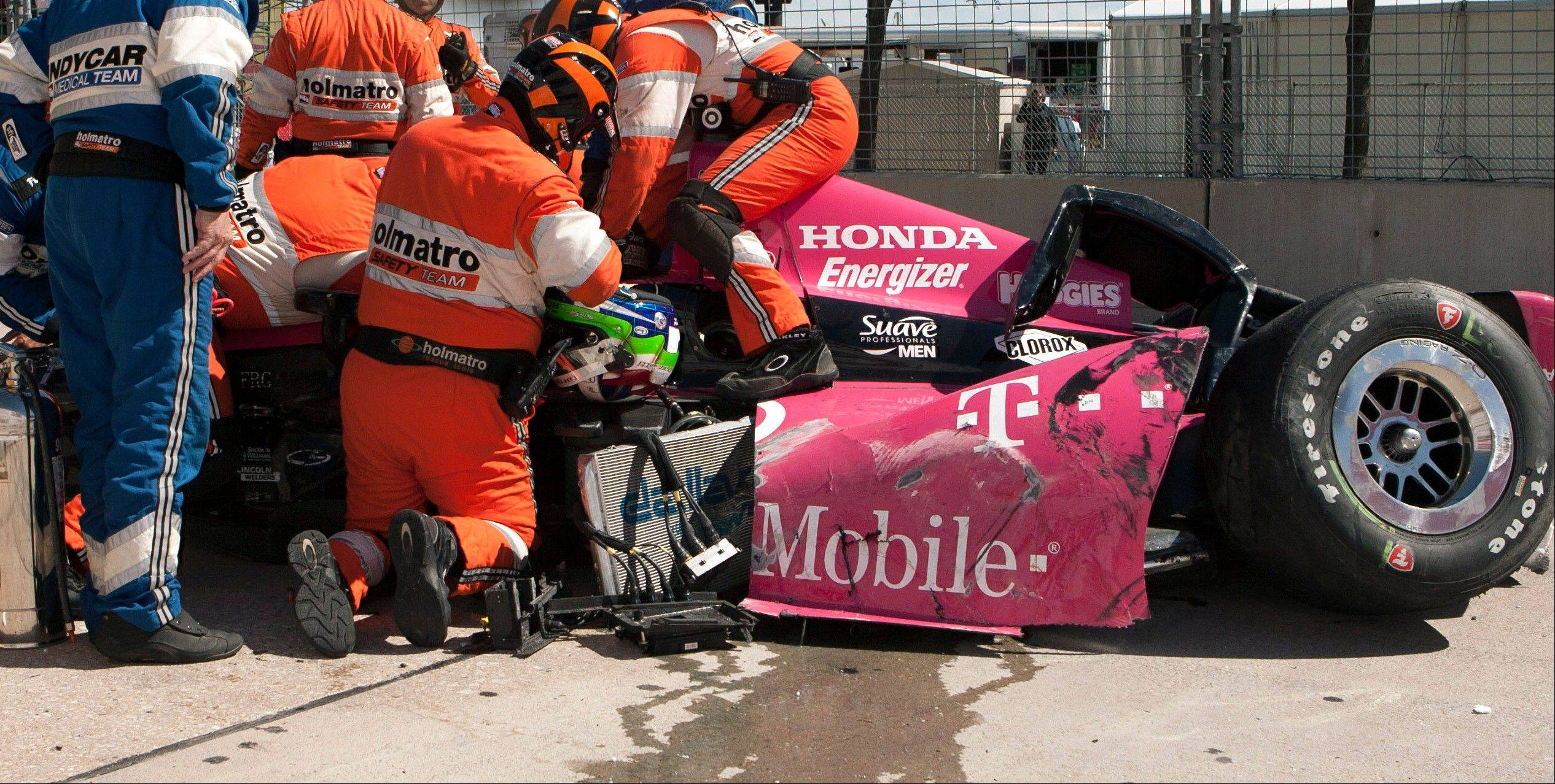 Safety team members work to remove Dario Franchitti, of Scotland, from his car after a crash during the second IndyCar Grand Prix of Houston auto race, Sunday, Oct. 6, 2013, in Houston.