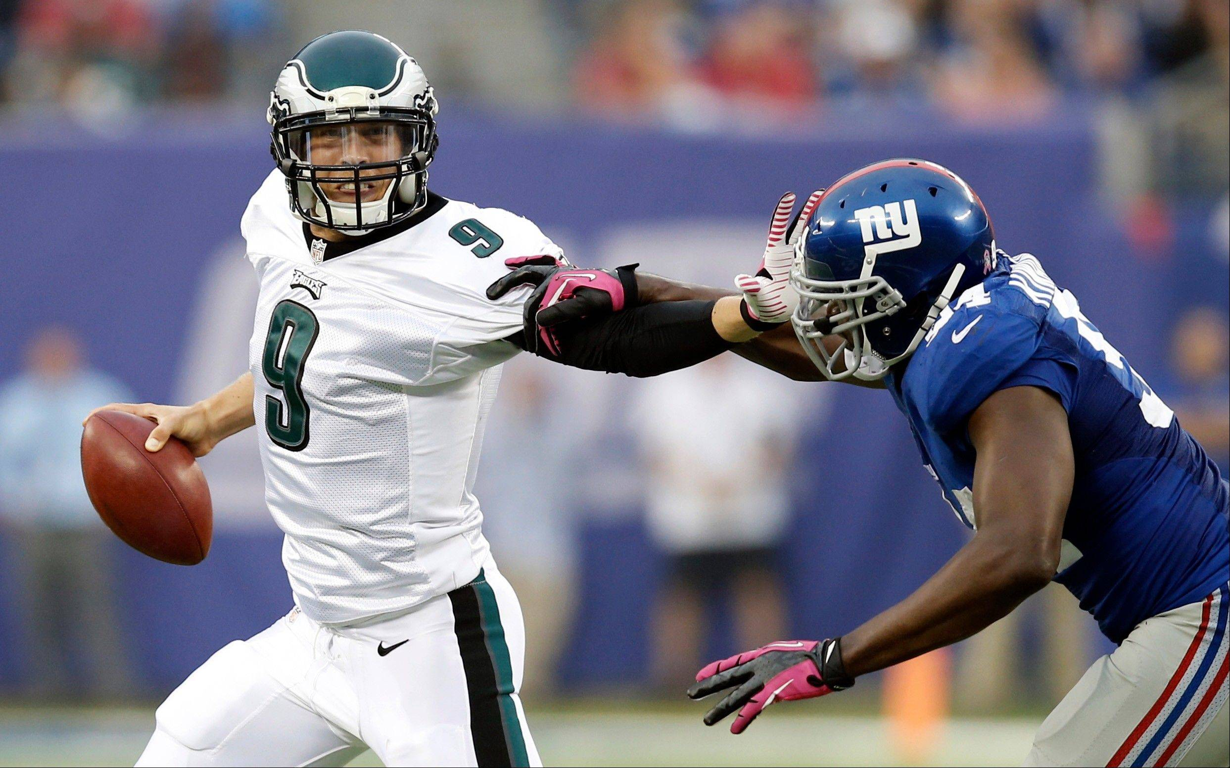 Philadelphia Eagles� Nick Foles (9) stiff-arms New York Giants� Mathias Kiwanuka (94) during the second half of an NFL football game on Sunday, Oct. 6, 2013, in East Rutherford, N.J.