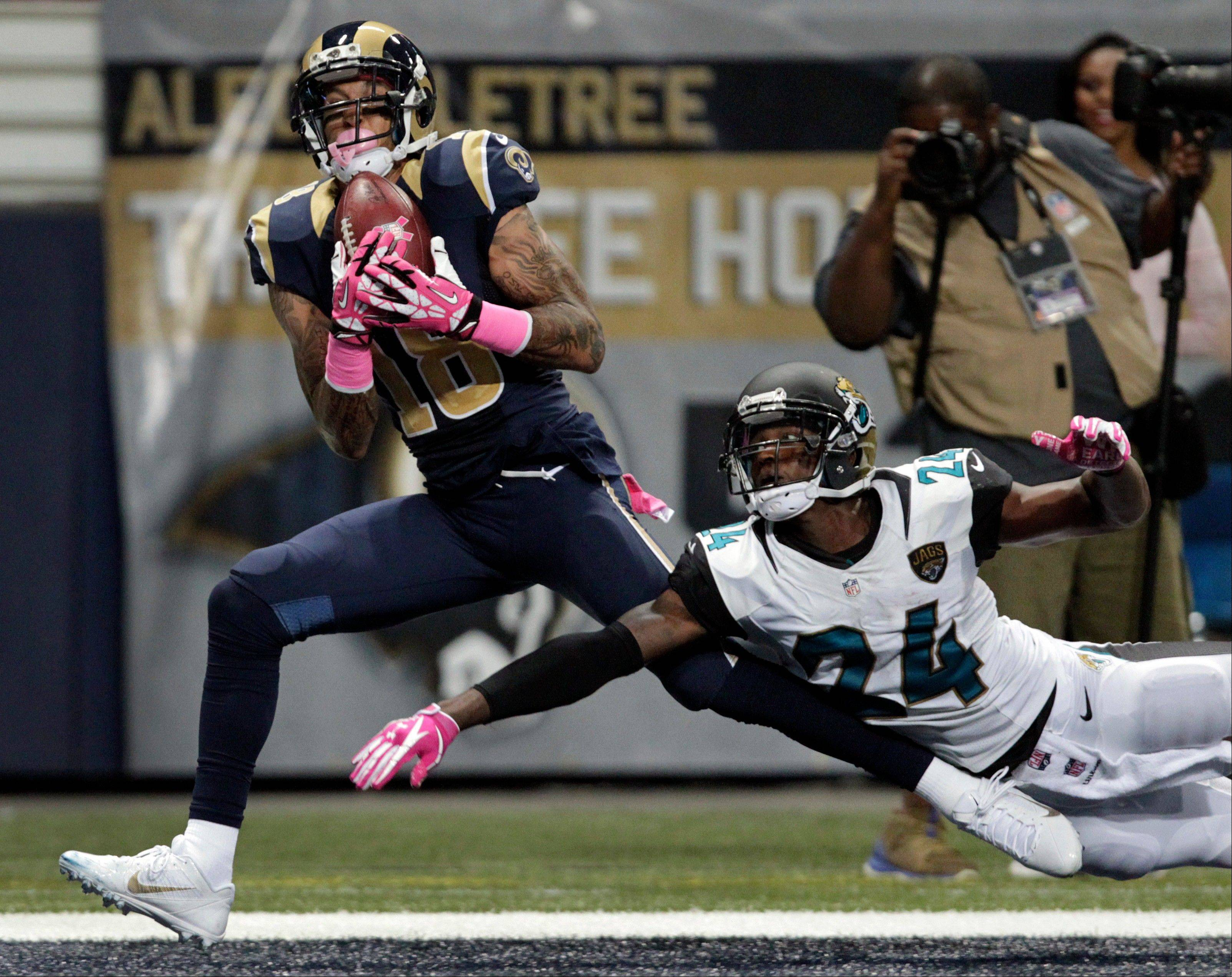 St. Louis Rams wide receiver Austin Pettis, left, catches a 31-yard pass for a touchdown as Jacksonville Jaguars defensive back Will Blackmon defends during the fourth quarter of an NFL football game Sunday, Oct. 6, 2013, in St. Louis.