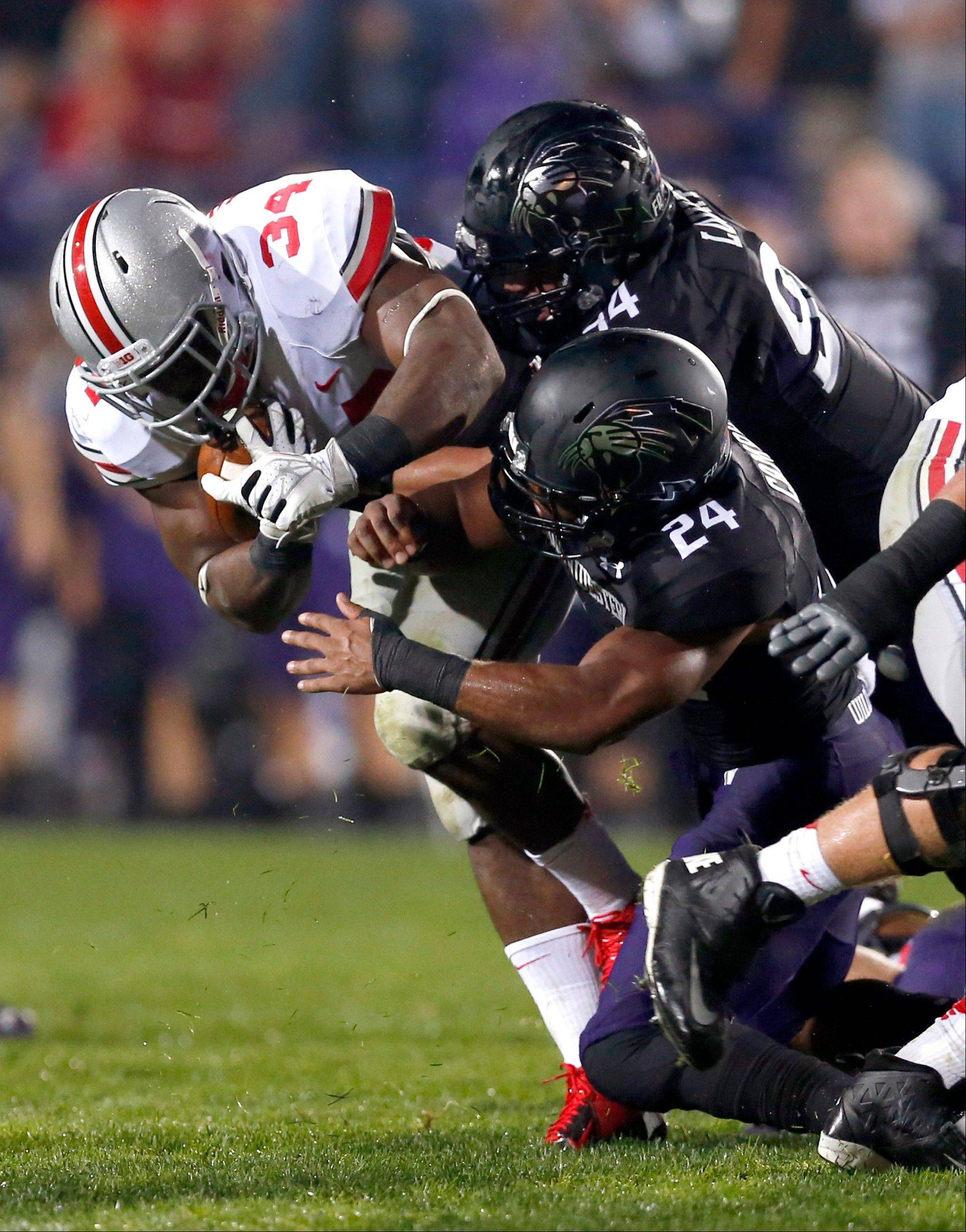 Ohio State running back Carlos Hyde (34) carries the ball and is tackled by Northwestern defensive lineman Dean Lowry (94) and safety Ibraheim Campbell during Saturday�s game in Evanston. Ohio State beat Northwestern 40-30.