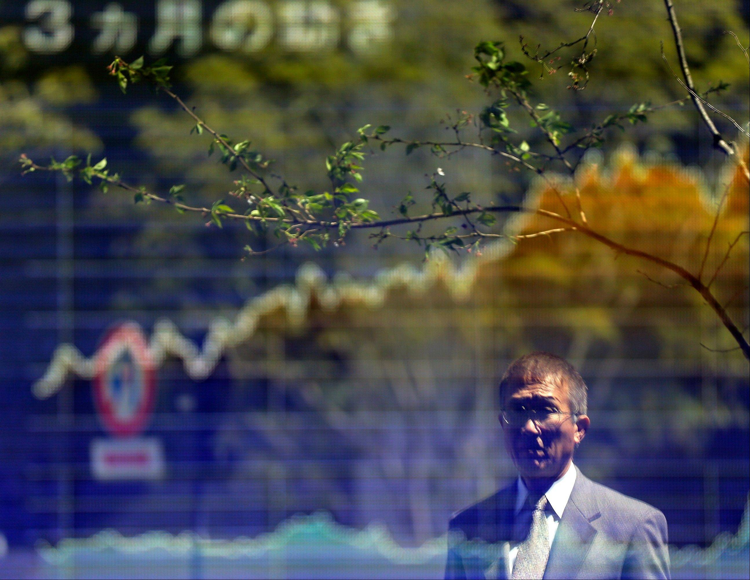A man looks at an electronic stock board in Tokyo. The Japanese have cut back 4 percent of their collective borrowing since before the financial crisis in 2007.