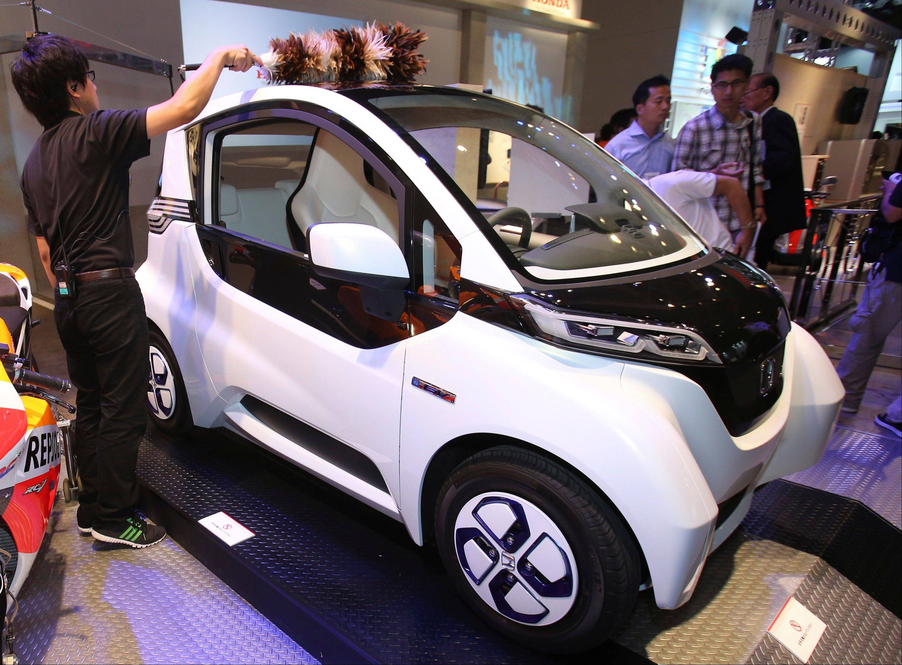An event staff cleans a Honda Motor Co.'s Micro Commuter prototype electric vehicle during the annual CEATEC advanced technologies exhibition in Chiba near Tokyo. By connecting the driver's smartphone to the dashboard, he or she can control the home electronics as television sets, fans, and electric lights while driving the vehicle.