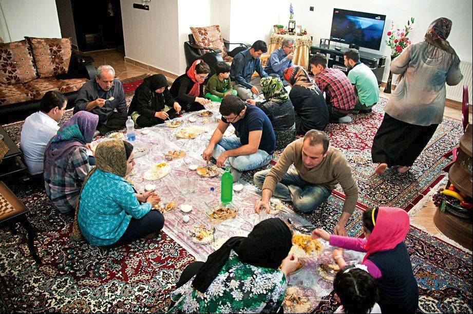 "The book ""Iranian Living Room"" peers behind the curtains of domestic life. Here, a traditional Iranian family dinner is shown."