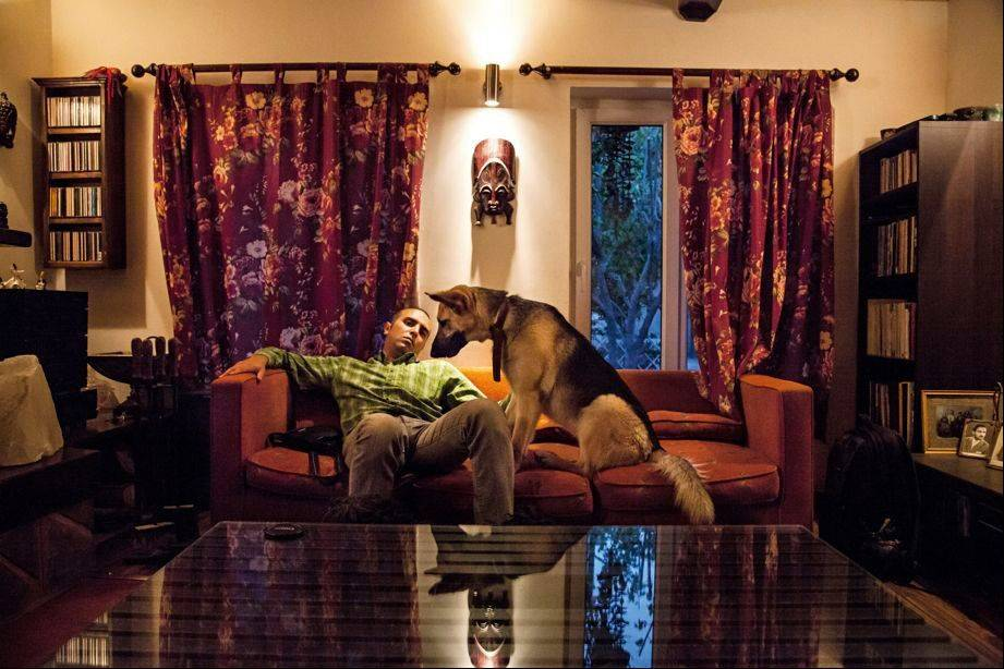 "Mohammad at home with his dog Loosy. Walking man's best friend is prohibited in public. From the book ""Iranian Living Room,"" which features the work of 15 young Iranian photographers."