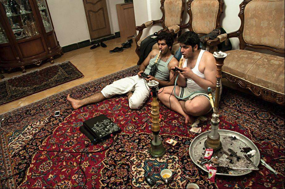 "Teenage boys playing video games and smoking hookah pipes at home in Tehran. ""Iranian Living Room"" portrays everyday home life for Iranians from a range of cultural, economic and religious backgrounds."