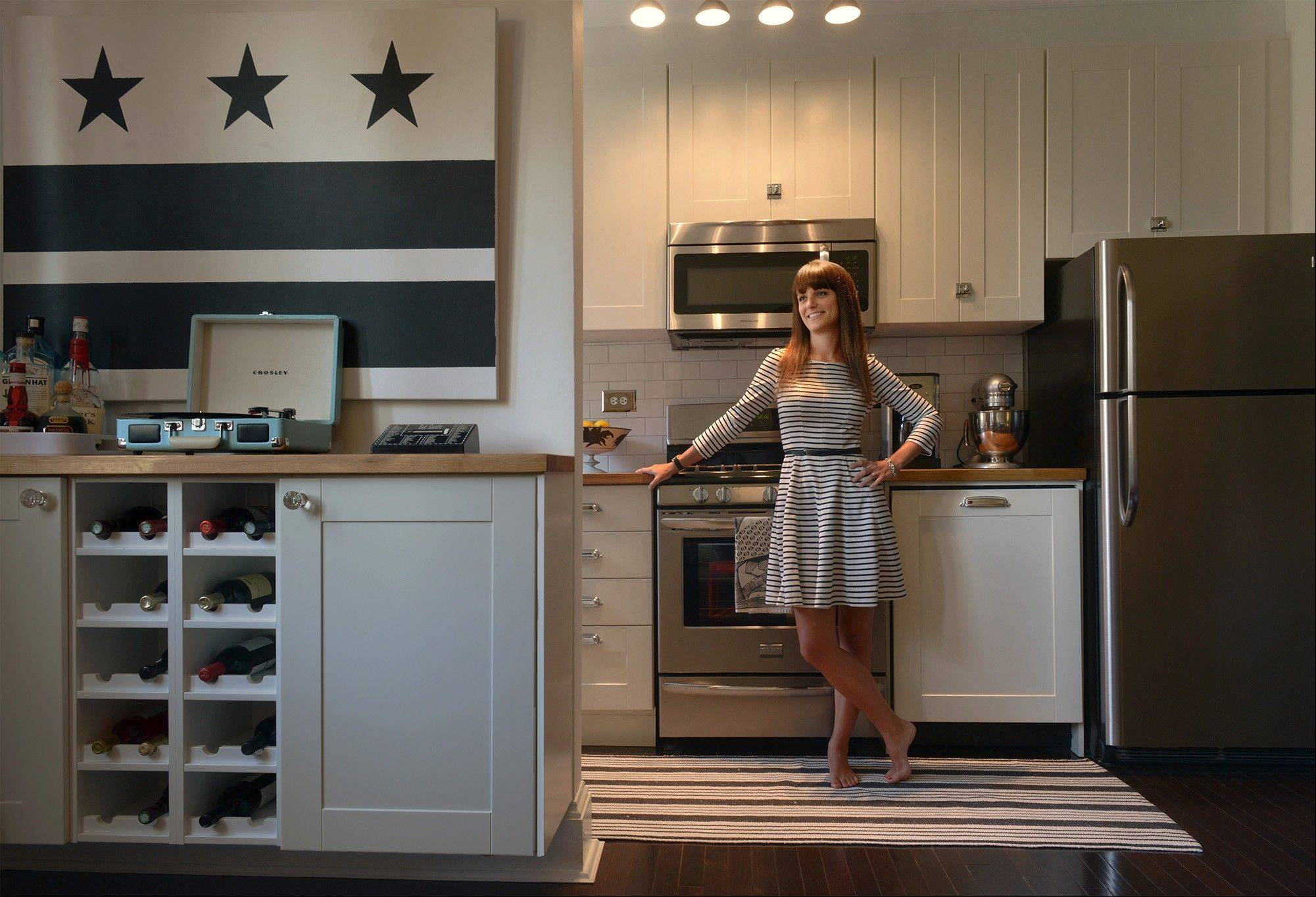 Kiera Kushlan in the renovated kitchen of the 750-square-foot co-op she shares with her husband Michael, who painted the black-and-white D.C. flag; the flag has been such a conversation piece itís now selling on Etsy.