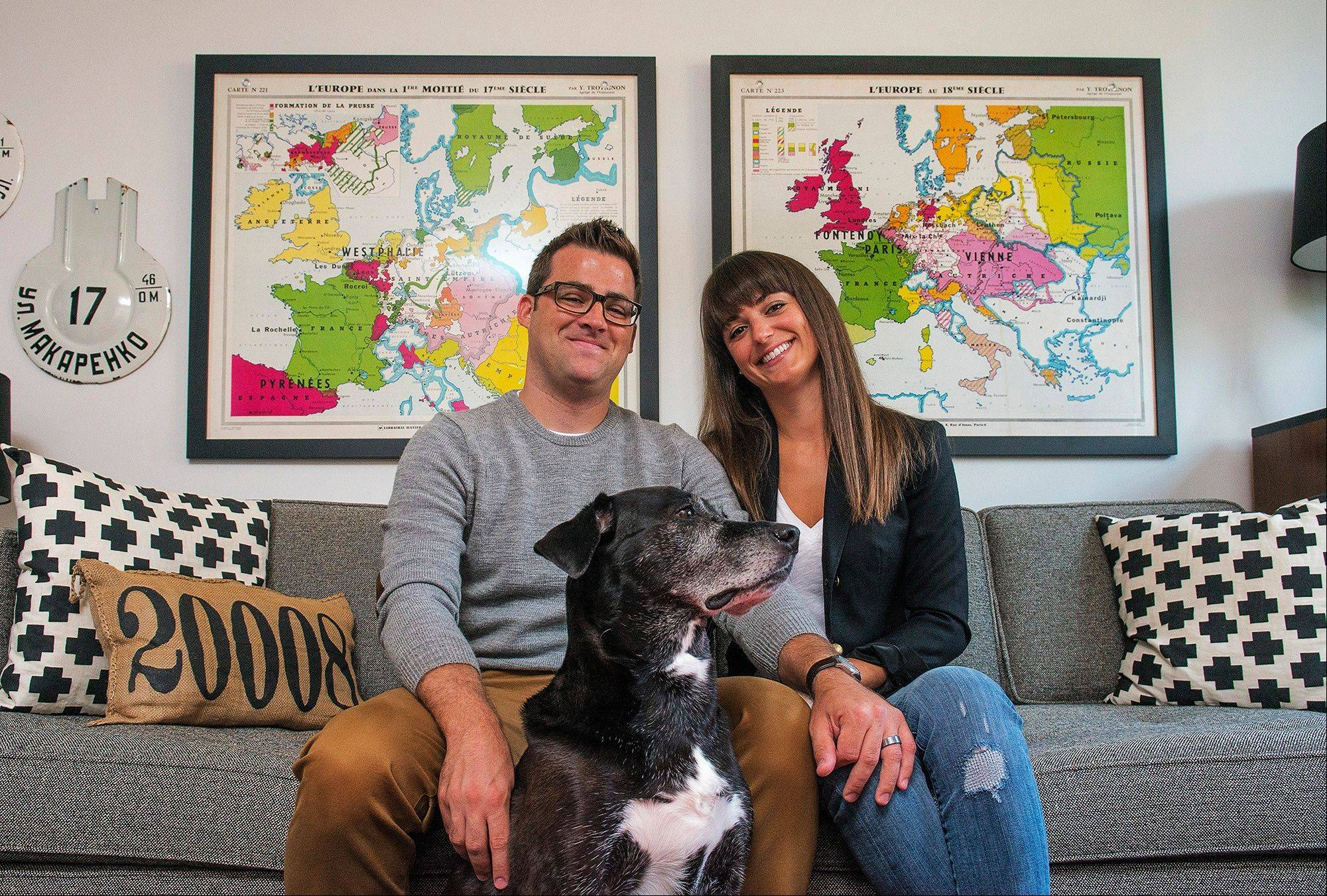The Kushlans and their dog, Copeland, in their living room under the maps the couple picked up on a trip to France; the Kushlans believe that what you leave out of a room is just as important as what you put in it.