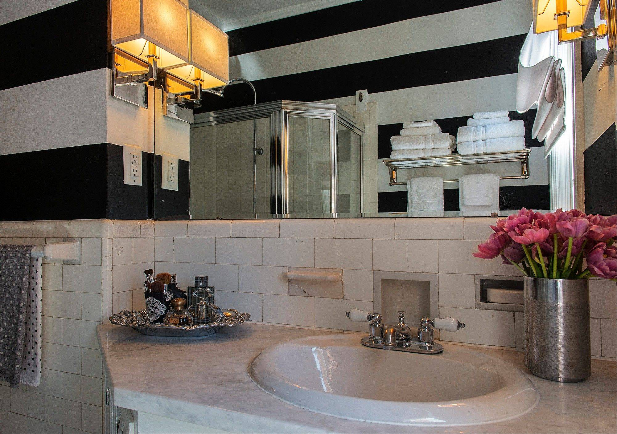 The vintage bathroom in the Kushiansí co-op got a budget makeover. The couple painted wide black and white stripes and added new lighting and a towel bar.