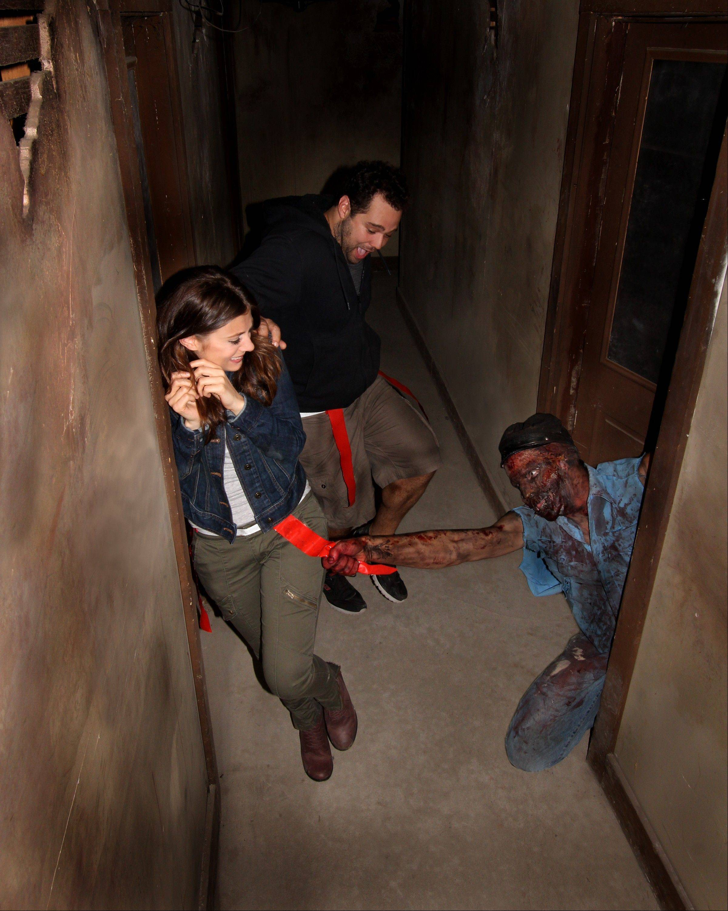 ASSOCIATED PRESS/SHOCKTOBERFEST An actor portraying a zombie grabs a flag from the belt of someone walking through the Prison of the Dead Escape, part of the Shocktoberfest attraction in Reading, Pa.