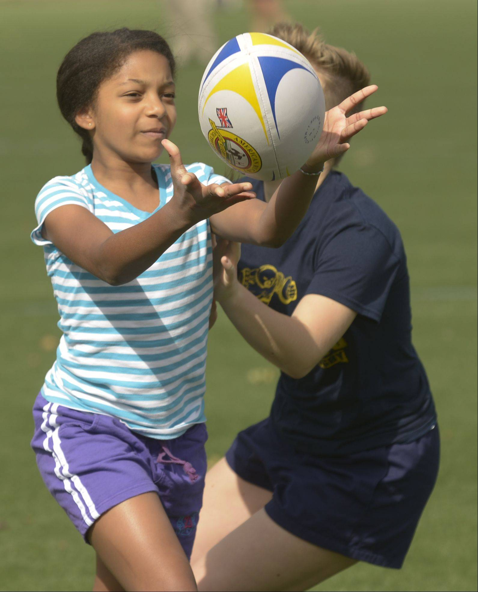 Anaise Fitzpatrick, 10, of Lake Villa practices catching a ball Sunday during the Girls Day of Rugby hosted by the Illinois Youth Rugby Association at Olympic Park in Schaumburg.
