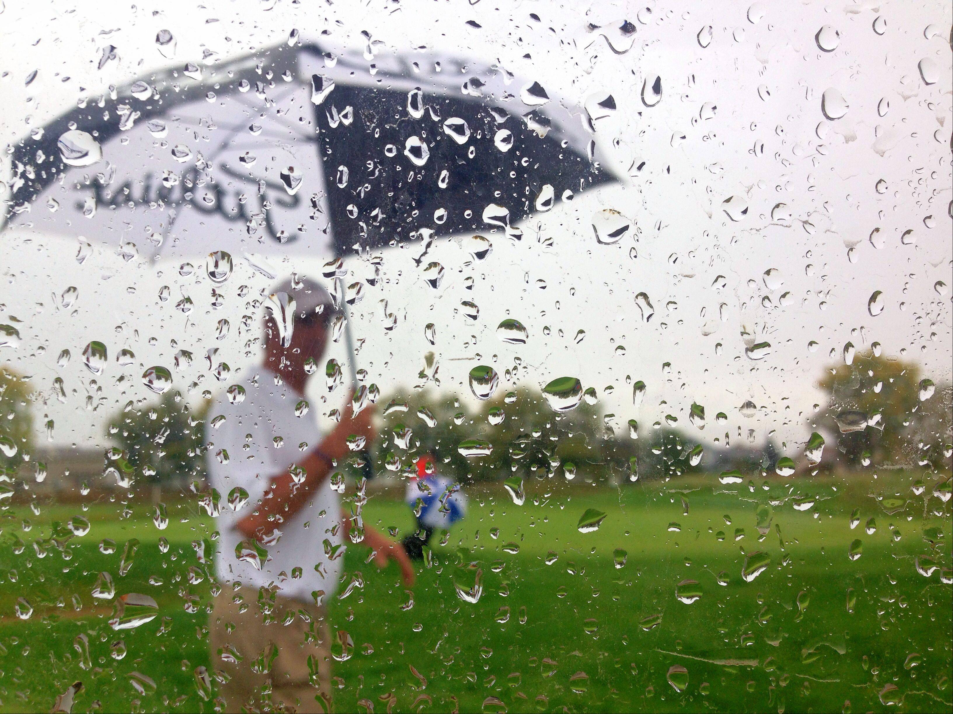 A golf spectator makes his way around a very soggy Golf Club of Illinois Thursday morning while watching action during the Fox Valley Conference boys golf tournament. Rain showers hit just about every part of the suburbs Thursday.