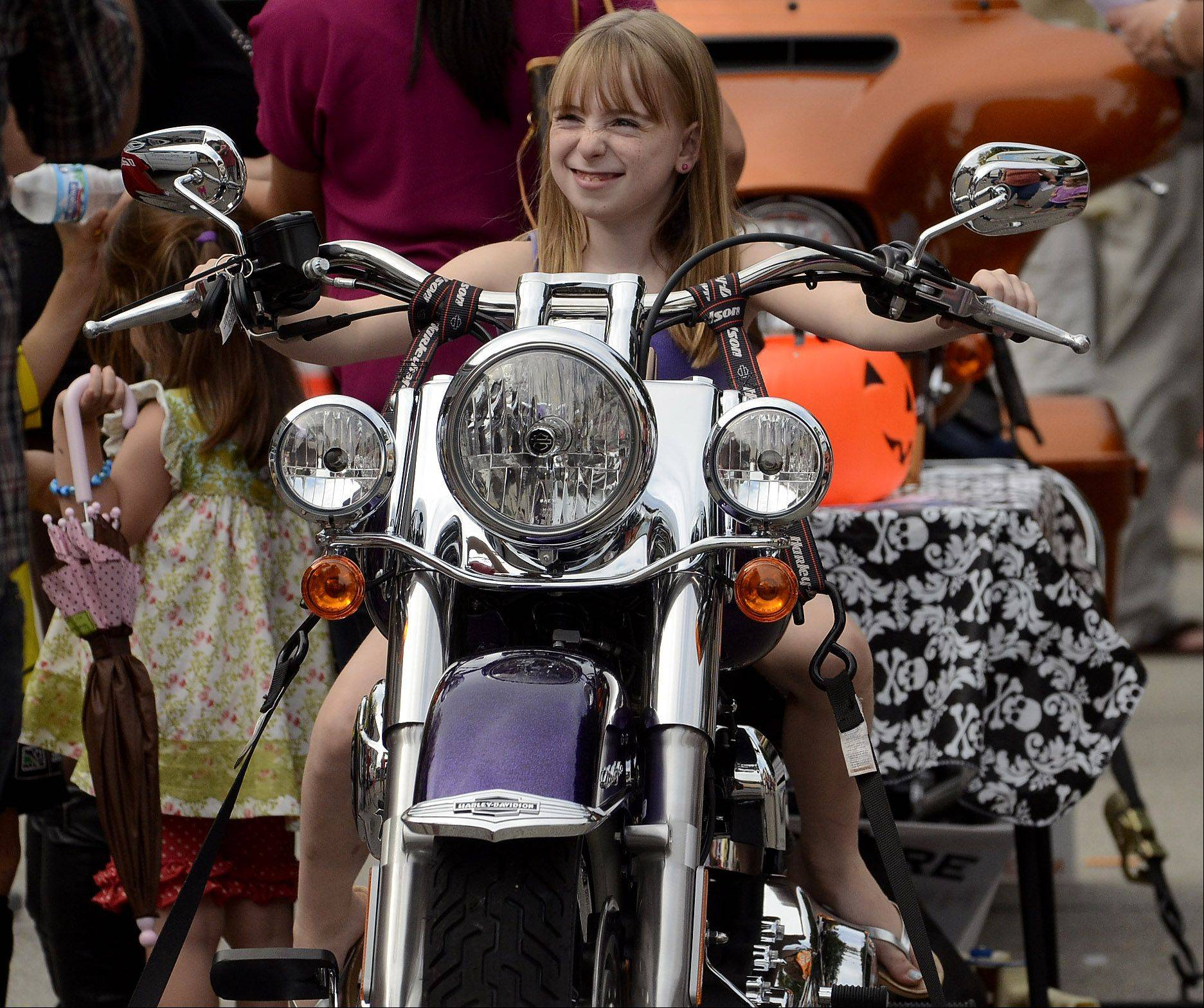 8-year-old Mia Lacey, of Libertyville, gets to sit atop a motorcycle courtesy of Lake Shore Harley-Davidson at the Libertyville Pumpkin Fest.