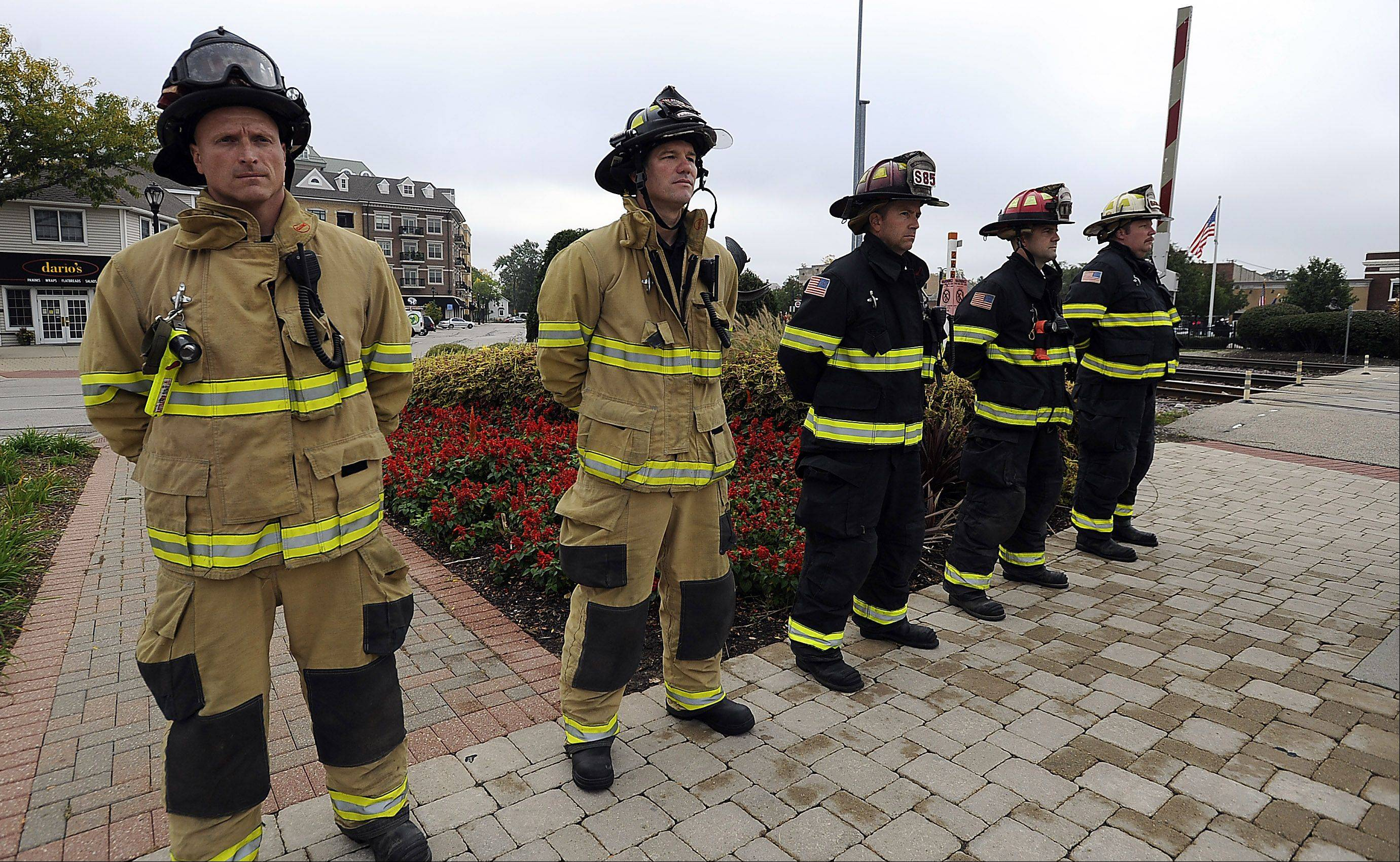 Palatine firefighters stand at attention near the railroad crossing in downtown Palatine during Tuesday morning's ceremony at the Firefighter's Memorial, honoring two volunteer firefighters who died in the line of duty on October 1, 1946 when their fire truck was hit by a Chicago and Northwestern Railroad passenger train.