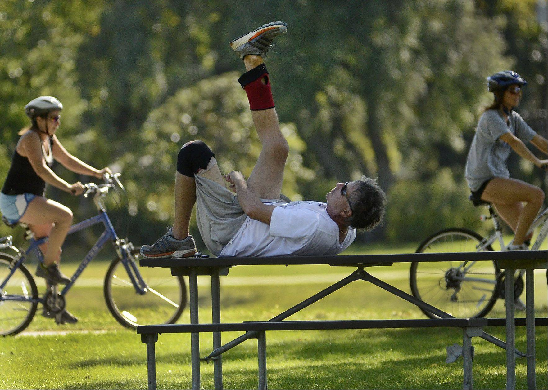 Robert Beelen, of Wheeling, uses a picnic table to stretch out his hamstrings after a walk around Lake Arlington in Arlington Heights. Beelen would walk the two-mile route daily until he injured his knee.