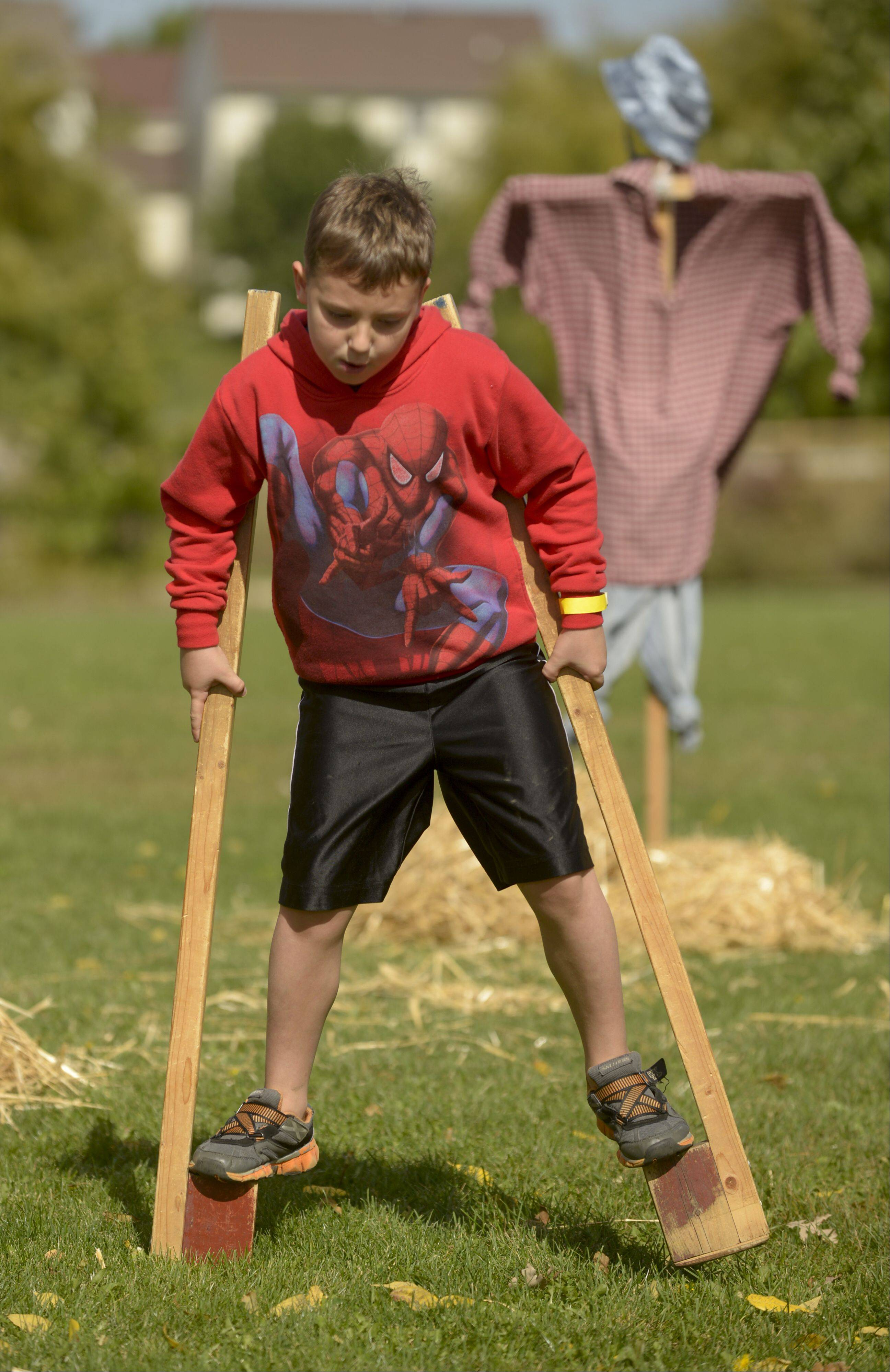 Drake Shaw, 6, of Lindenhurst tries using stilts Sunday while visiting the Bonner Heritage Farm's Country Fair in Lindenhurst. The event featured wagon rides, crafts, games and a petting zoo on an 1842 farm.