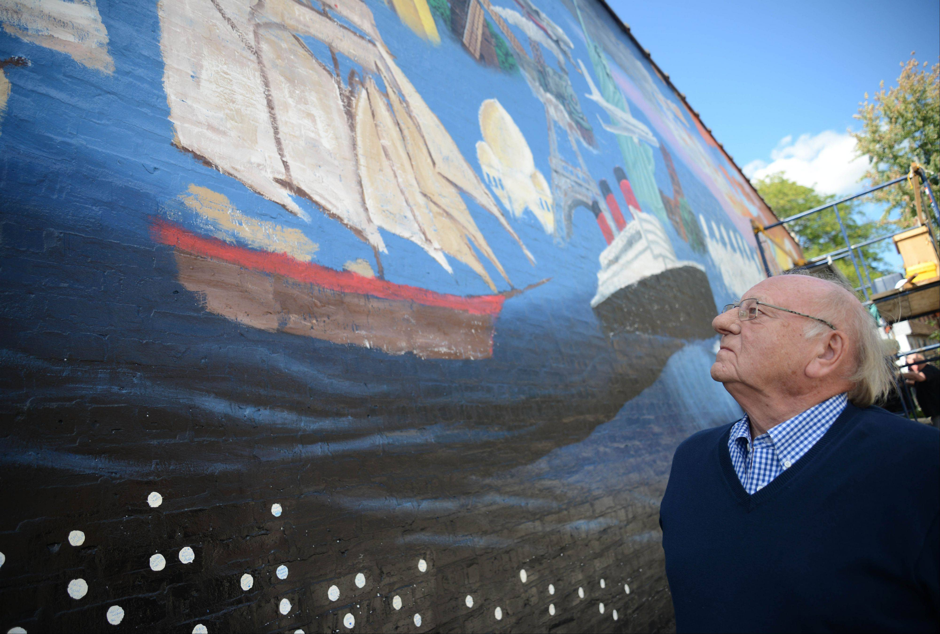 "Henry Schnabel of Wheaton examines the new mural, ""Pearls of the Universe"" unveiled in the village Sunday. The 70-foot mural, created by artist R.J. Ogren celebrates diversity in Wheaton. It was inspired by a poem written by Mehret Asgedom, who came to Wheaton as an Ethiopian refugee when she was a child."