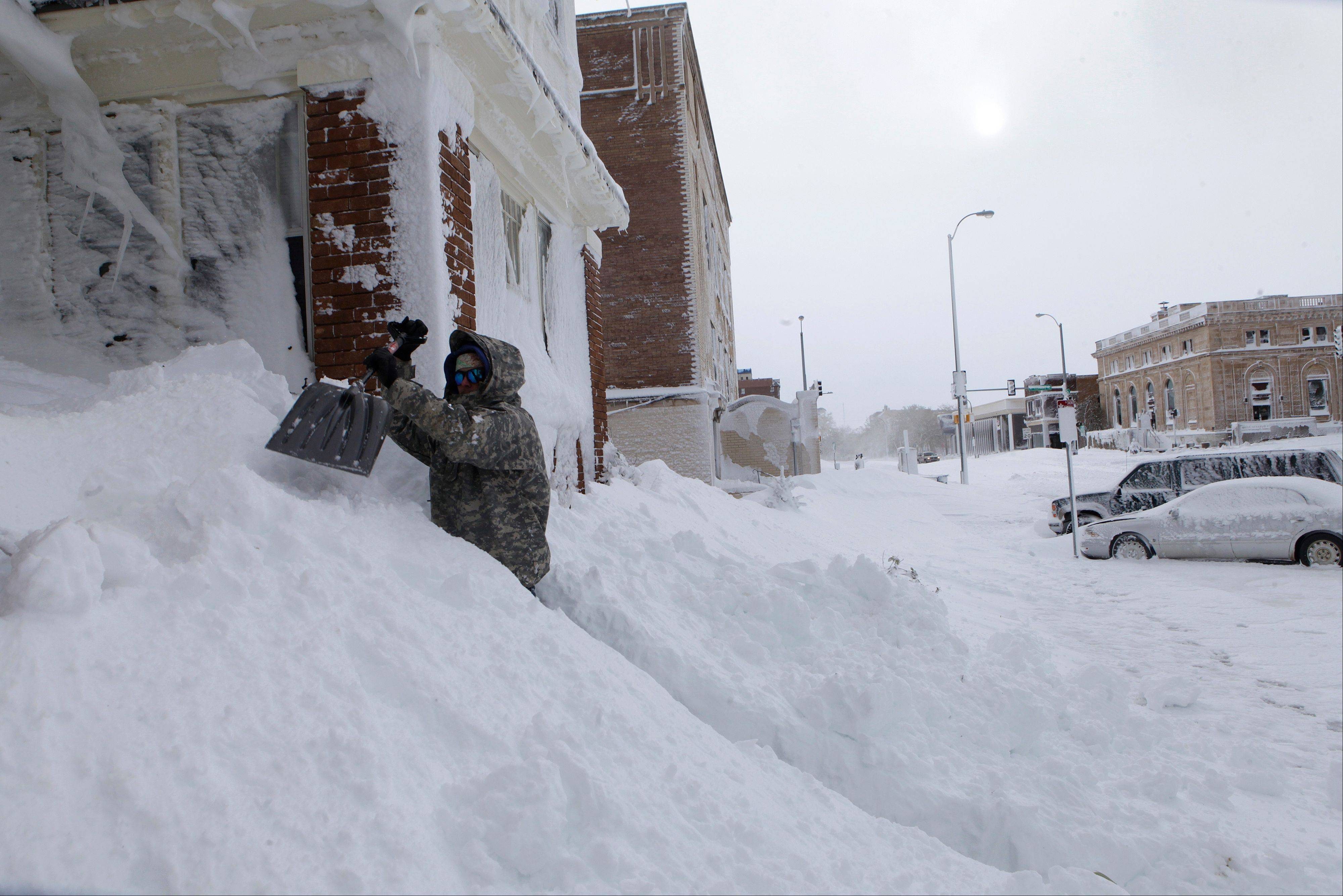 Chad Hoffman clears snow from the entrance to his apartment building in Rapid City, S.D,, Saturday. A storm dumped at least three and a half feet of wet, heavy snow in the Black Hills. Rapid City had 21 inches, but 31 inches were recorded just a mile southwest of the city.