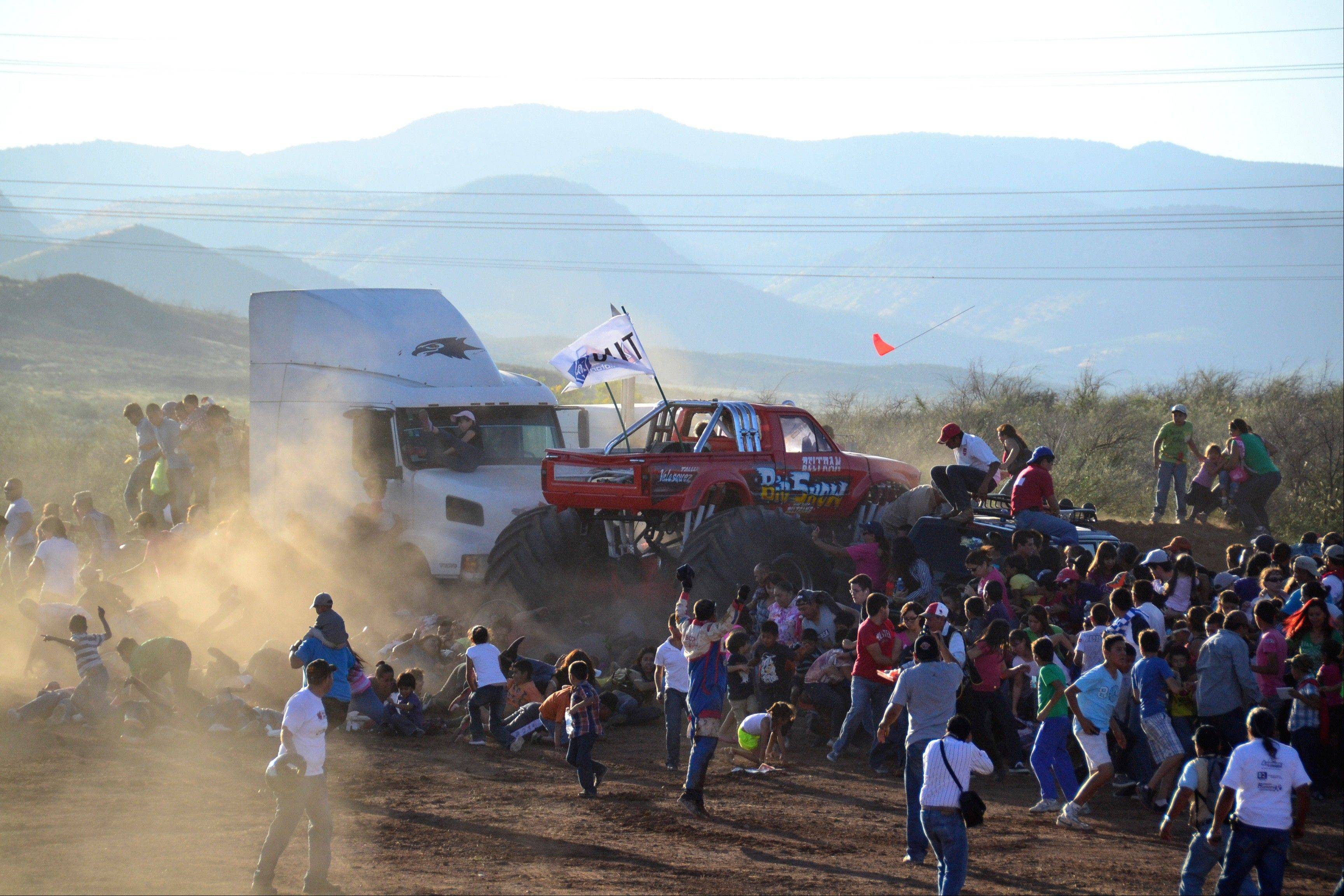 People run as an out of control monster truck plows through a crowd of spectators at a Mexican air show in the city of Chihuahua, Mexico, Saturday. According to authorities, at least 8 people were killed and dozens were injured.