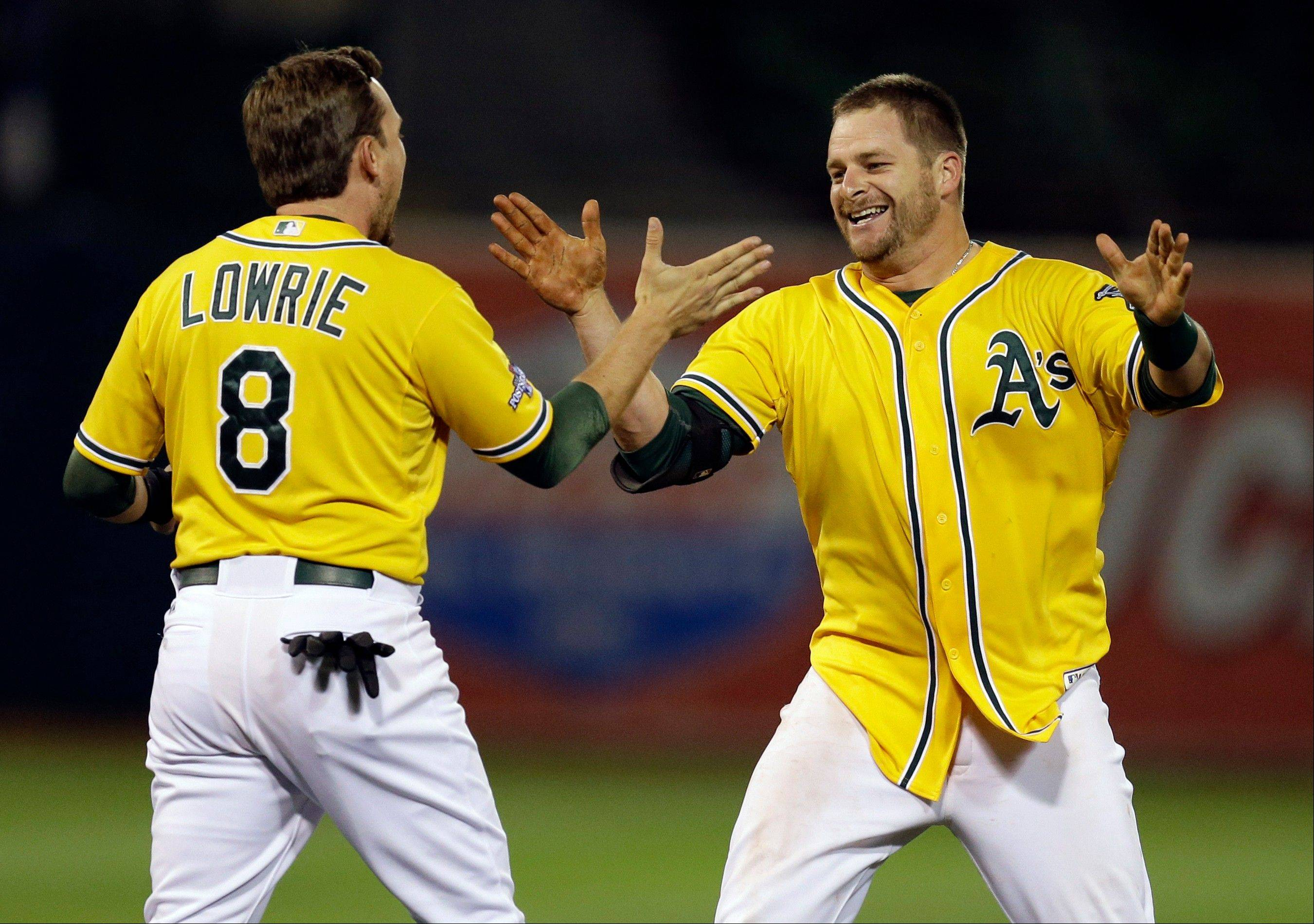 Oakland Athletics Stephen Vogt is congratulated by teammate Jed Lowrie after Vogt made the game winning hit in the bottom of the ninth inning to beat the Detroit Tigers 1-0 in Game 2 of an American League baseball Division Series Saturday night in Oakland, Calif.