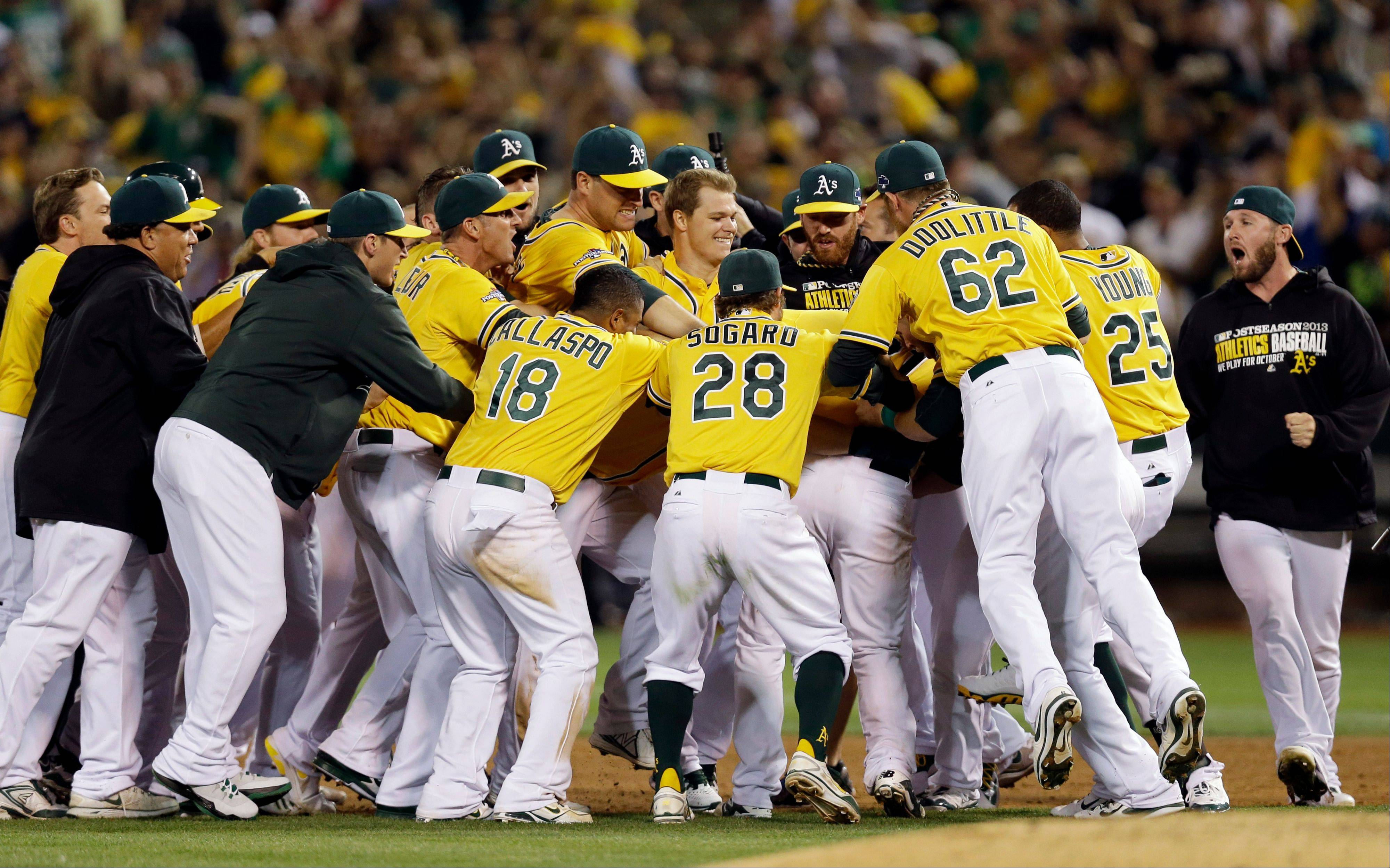 The Oakland Athletics celebrate their 1-0 win over the Detroit Tigers in Game 2 of an American League baseball Division Series Saturday night in Oakland, Calif.