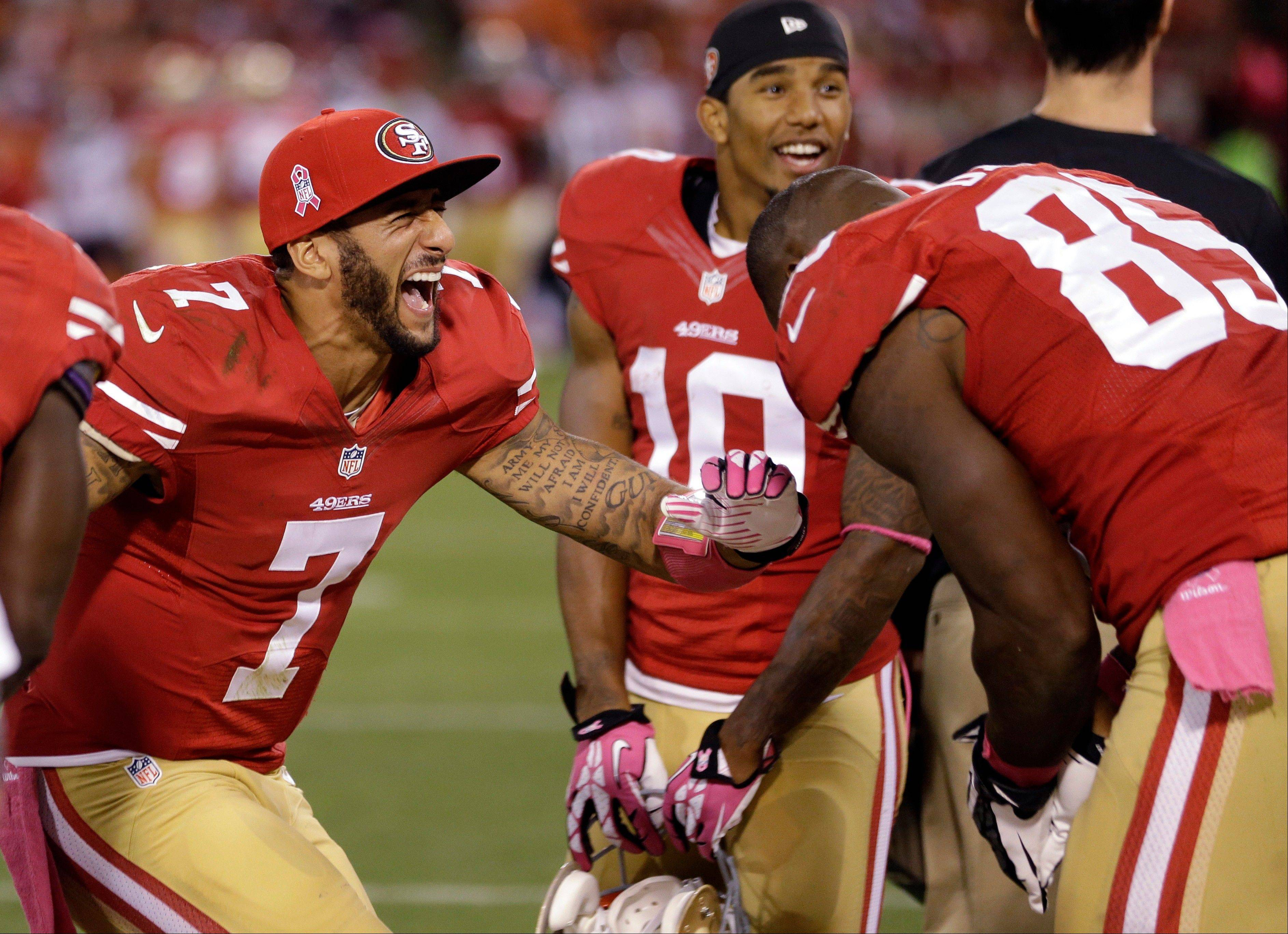 San Francisco 49ers quarterback Colin Kaepernick (7) and tight end Vernon Davis, right, laugh after winning their game 34-3 against the Houston Texans during an NFL football game in San Francisco, Sunday, Oct. 6, 2013.