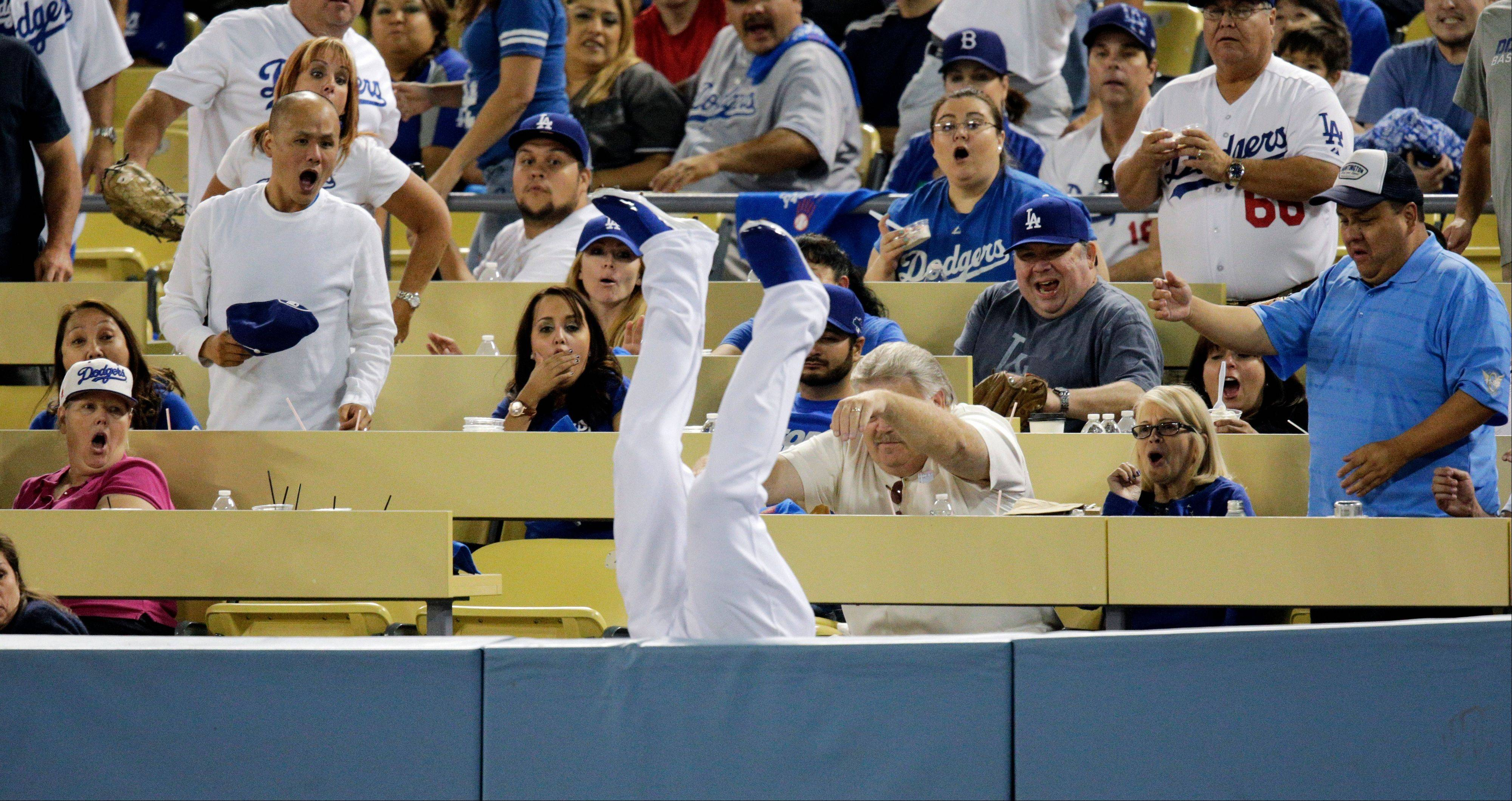 Fans react as Los Angeles Dodgers left fielder Carl Crawford falls upside down over the rail after catching a foul ball hit by Atlanta Braves' Justin Upton during the seventh inning in Game 3 of the National League division baseball series Sunday, Oct. 6, 2013, in Los Angeles.