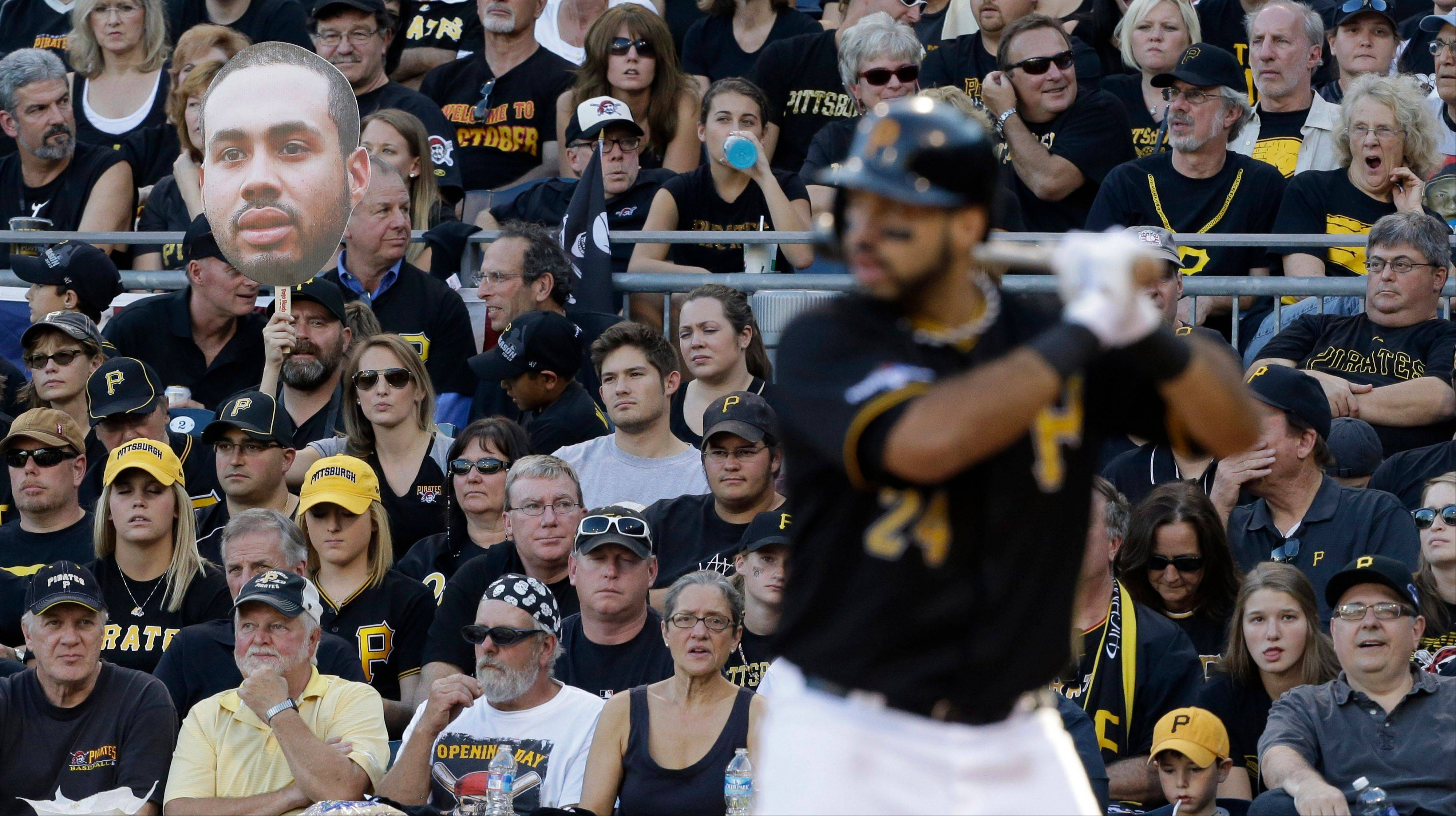 A fan holds a giant poster photo of Pittsburgh Pirates' Pedro Alvarez, left, as he bats in the fourth inning of Game 3 of a National League division baseball series against the St. Louis Cardinals on Sunday, Oct. 6, 2013 in Pittsburgh.