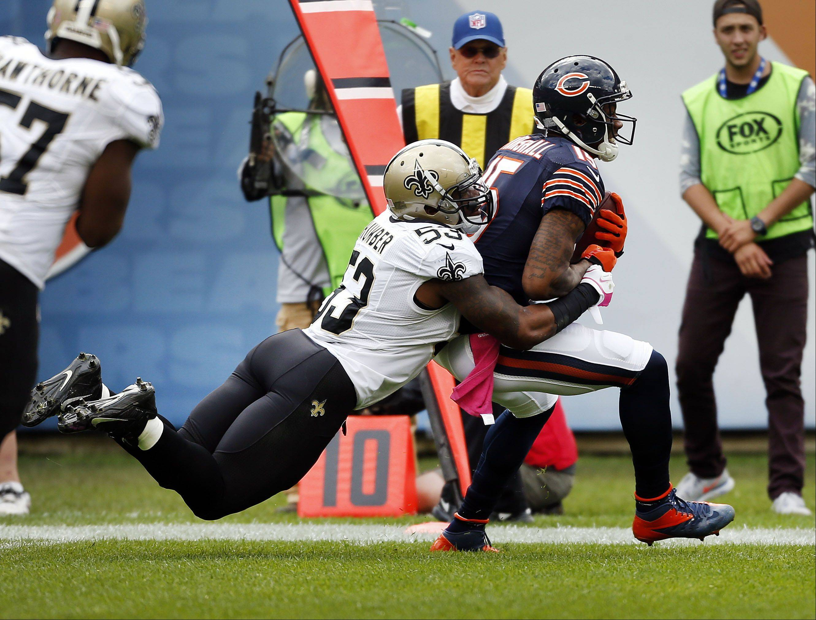 New Orleans Saints linebacker Ramon Humber tackles Chicago Bears wide receiver Brandon Marshall after a catch.