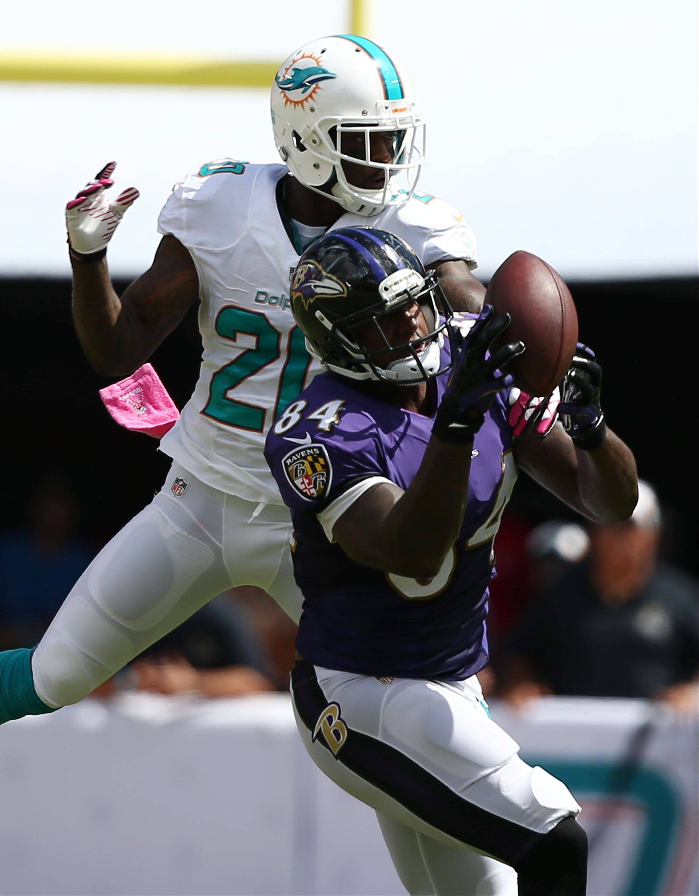 Baltimore Ravens tight end Ed Dickson (84) catches a pass over Miami Dolphins free safety Reshad Jones (20) during the first half of an NFL football game, Sunday, Oct. 6, 2013, in Miami Gardens, Fla.