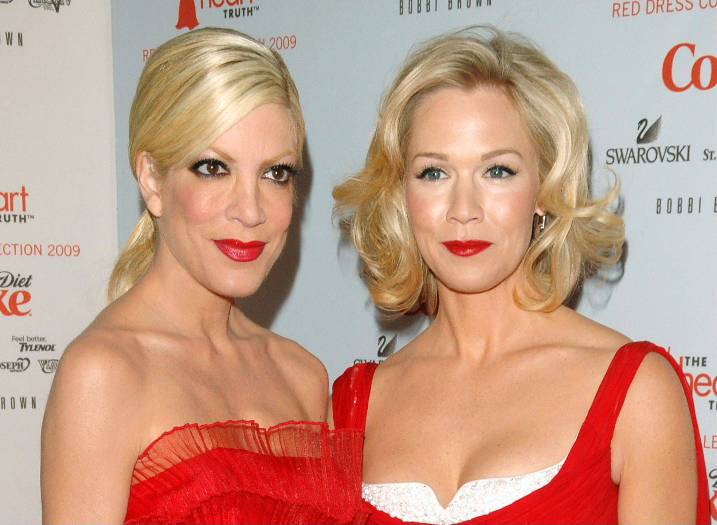 This Feb. 13, 2009 file photo shows actors Tori Spelling, left, and Jennie Garth at the Heart Truth�s Red Dress collection during Fashion Week in New York. The former �Beverly Hills, 90210� stars are reuniting. The actresses will co-star and executive produce the new ABC Family series �Mystery Girls.� In the series, Spelling and Garth play Holly and Charlie, who were on a crime-solving series in the 90�s that was the highest-rated show on TV. Spelling�s Holly is looking to reignite her fame and opens a detective agency. She persuades Charlie, now a suburban mom to help. �Mystery Girls� is set to shoot in November.