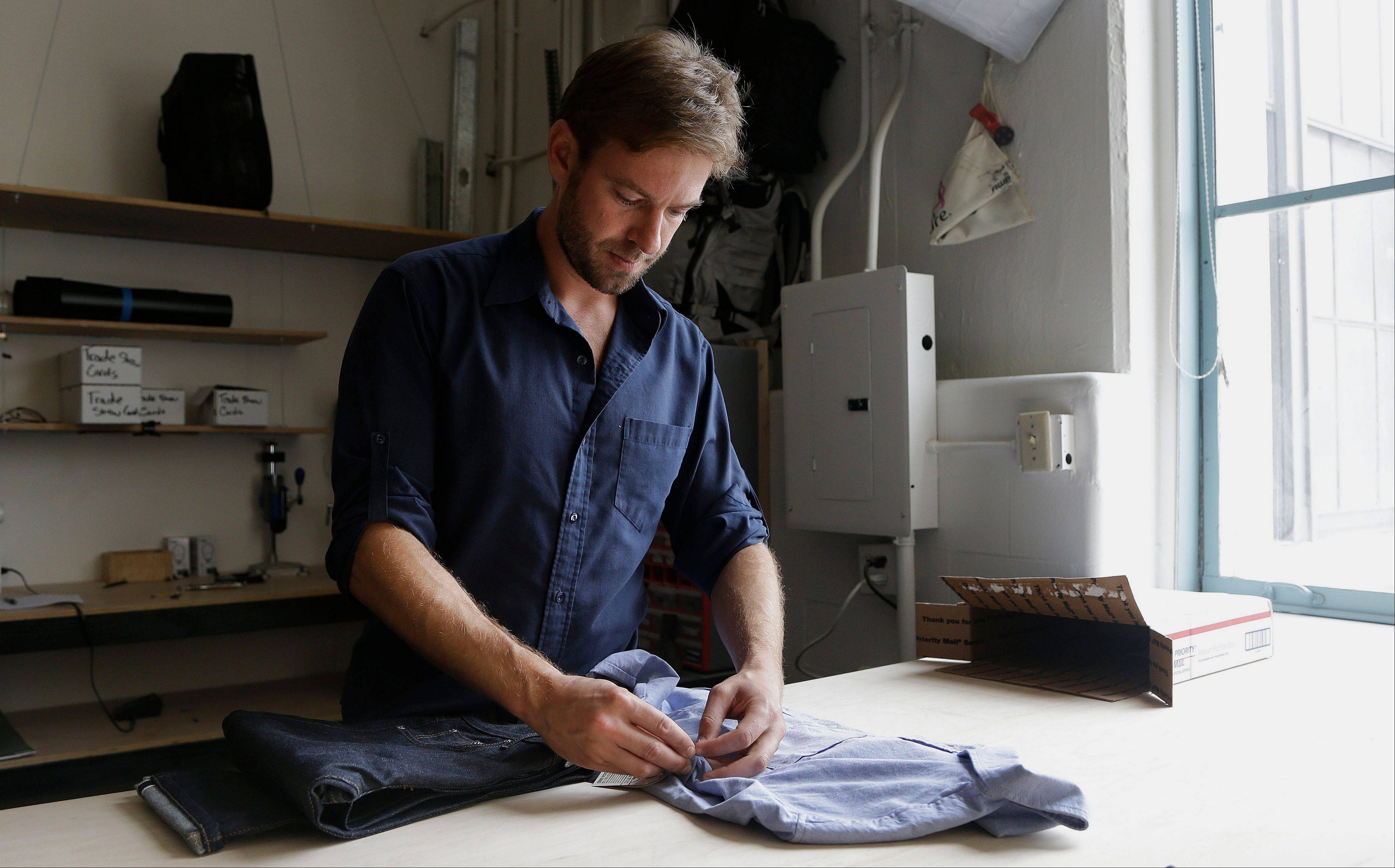 Peak Design founder Peter Dering looks through a package of clothing he had received from Buck Mason at his office in San Francisco. The Silicon Valley has a fashion problem dating back to its founders, who launched high tech companies promising to be different: no more top down management, no more cubicles, no more business suits.