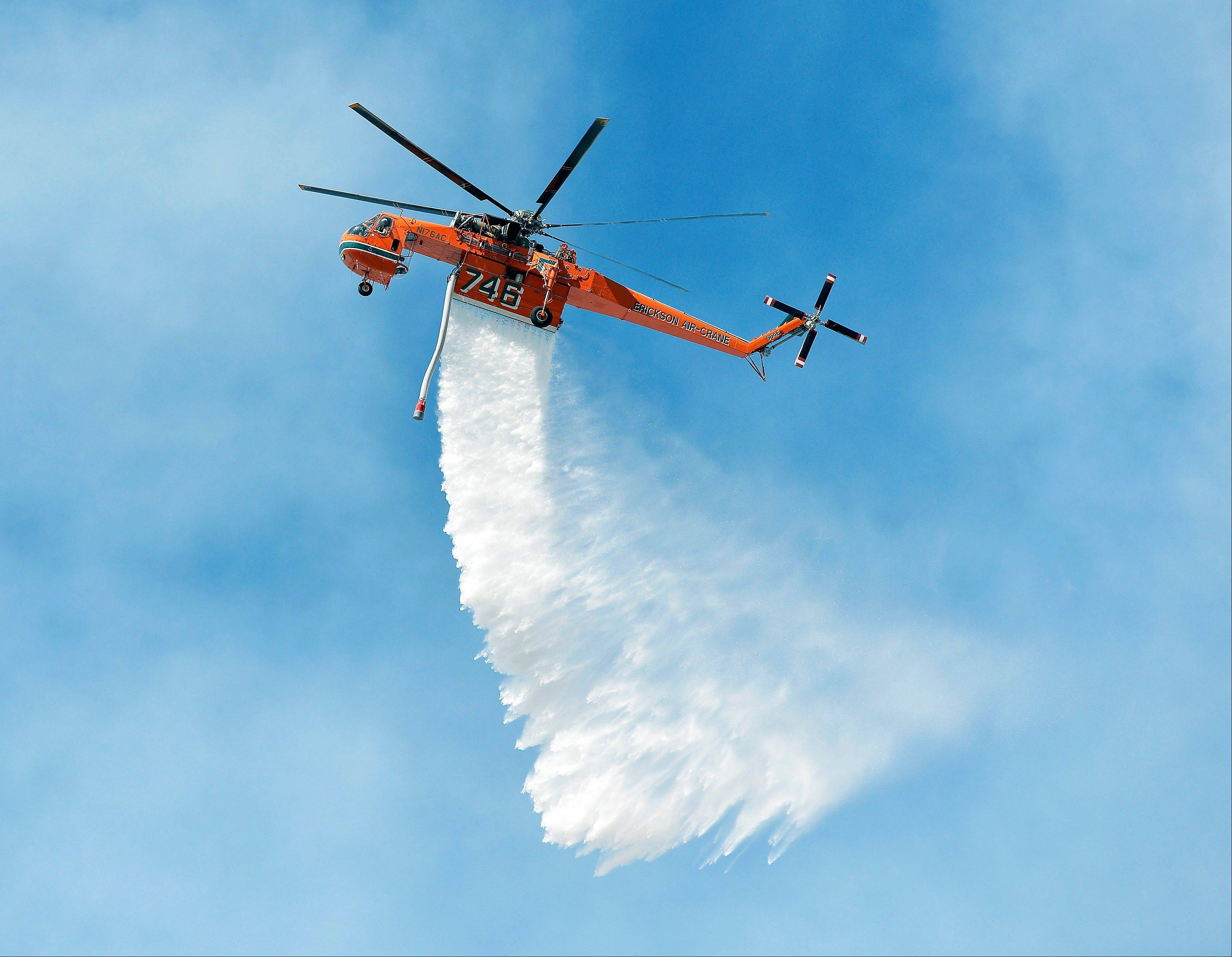 A Sikorsky firefighting helicopter makes a water drop on flames above Baker Canyon in Orange County, Calif. Sunday, Oct. 6, 2013. A mulch pile fire reported late Sunday morning quickly spread to surrounding wild vegetation, said Orange County Fire Authority Capt. Steve Concialdi. No homes were threatened.