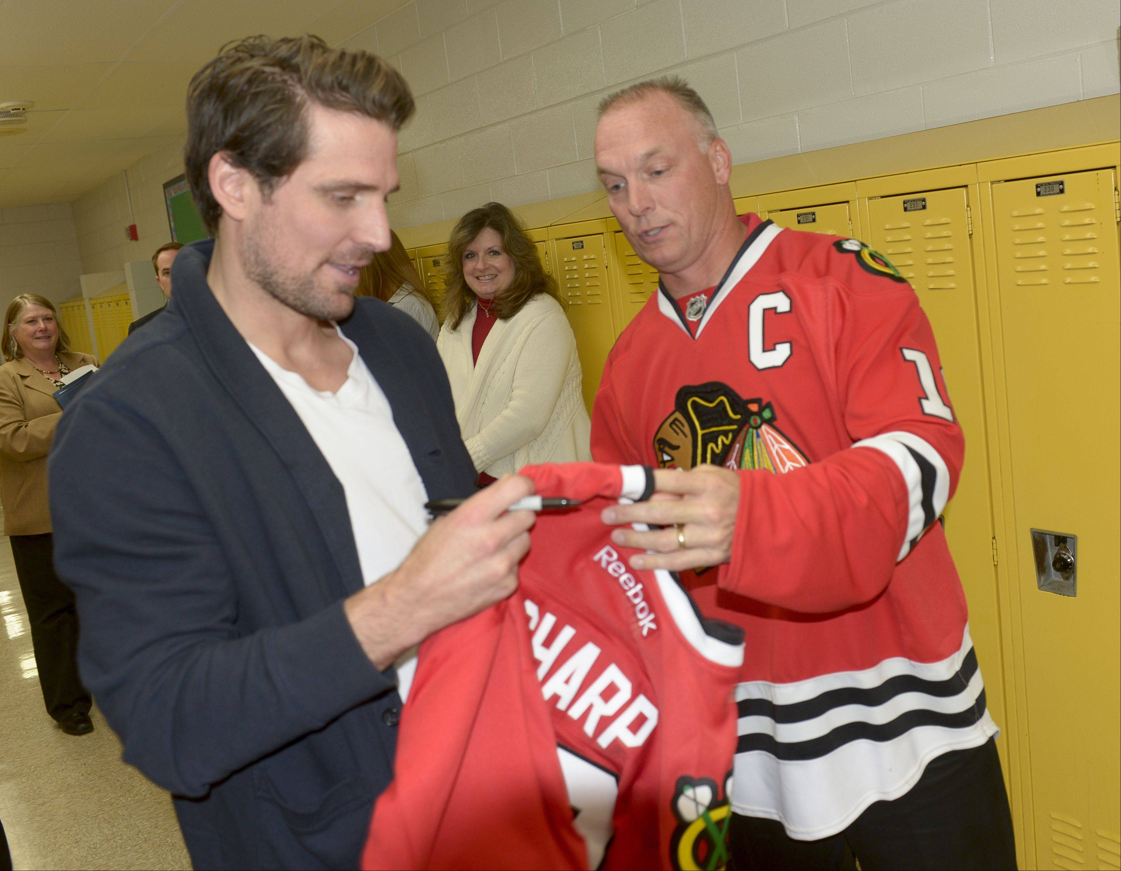 Technology teacher Pete Meyer has Patrick Sharp of the Chicago Blackhawks sign a jersey during Sharp's visit to Lisle Junior High School.