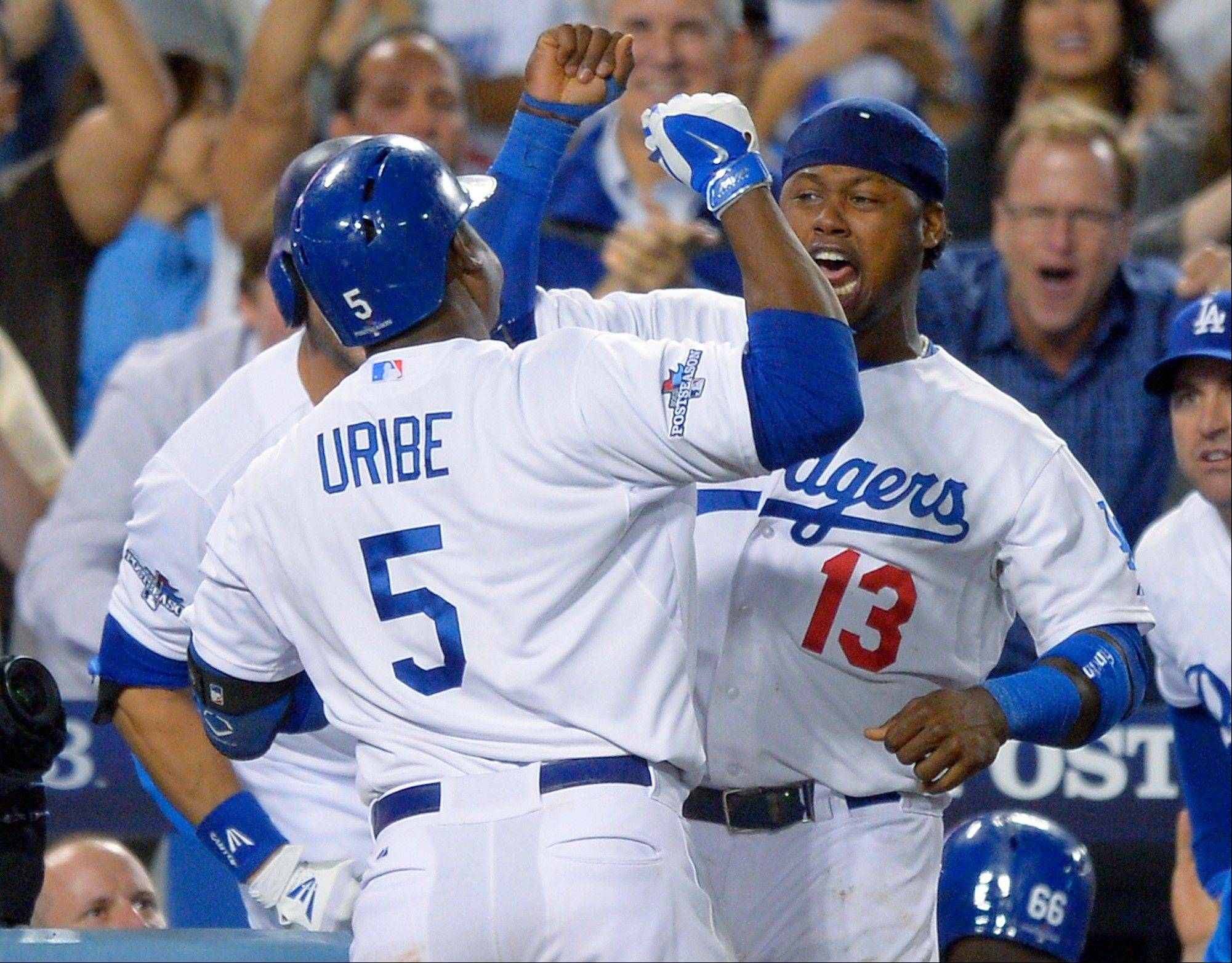 The Dodgers' Juan Uribe (5) celebrates with Hanley Ramirez (13) after Uribe hit a two-run home run in the eighth inning Monday in Game 4 in the National League Division Series against the Braves. The Dodgers won 4-3 at home.