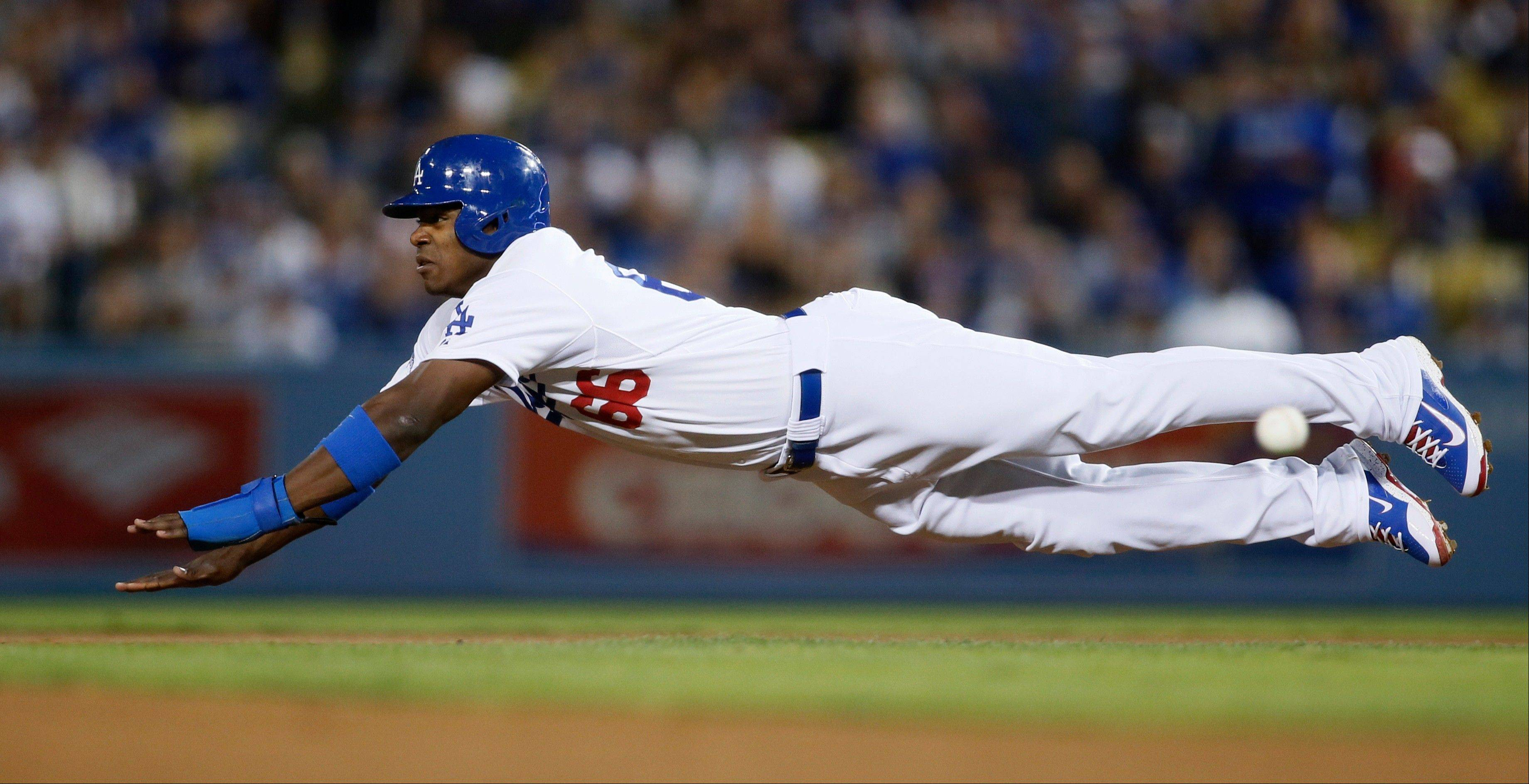 The Dodgers' Yasiel Puig dives for second base before being caught stealing in the fourth inning of Game 4.