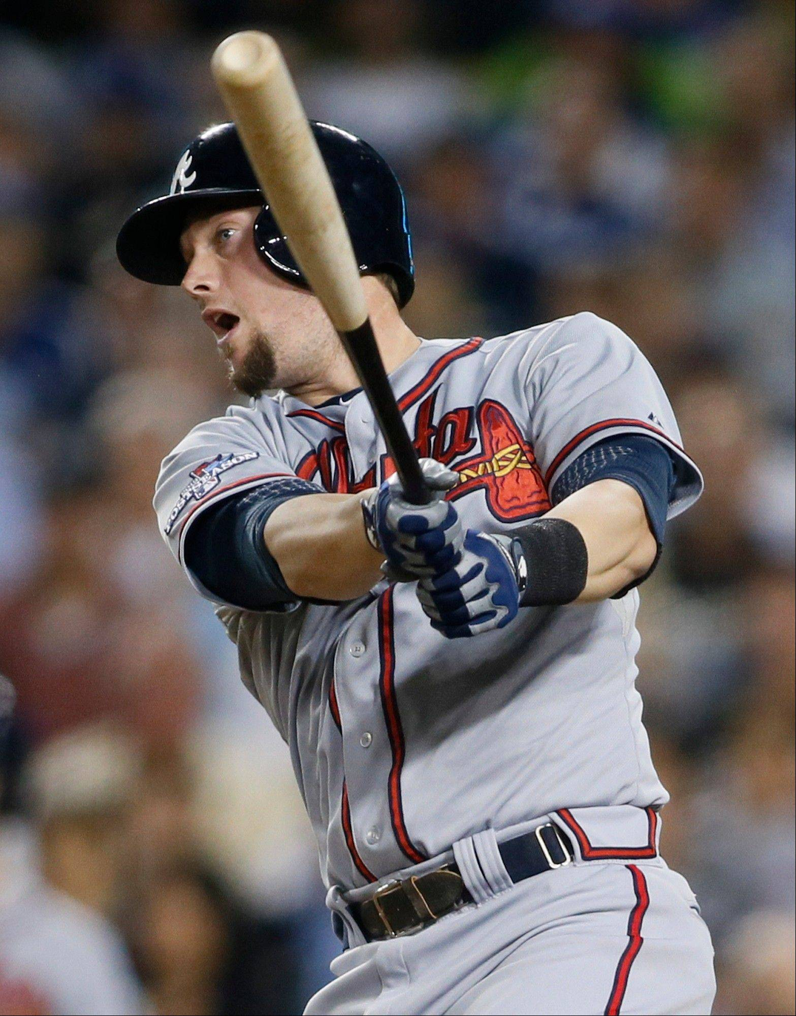 The Braves' Chris Johnson hits an RBI single to score Freddie Freeman in the fourth inning of Game 4 Monday in Los Angeles.