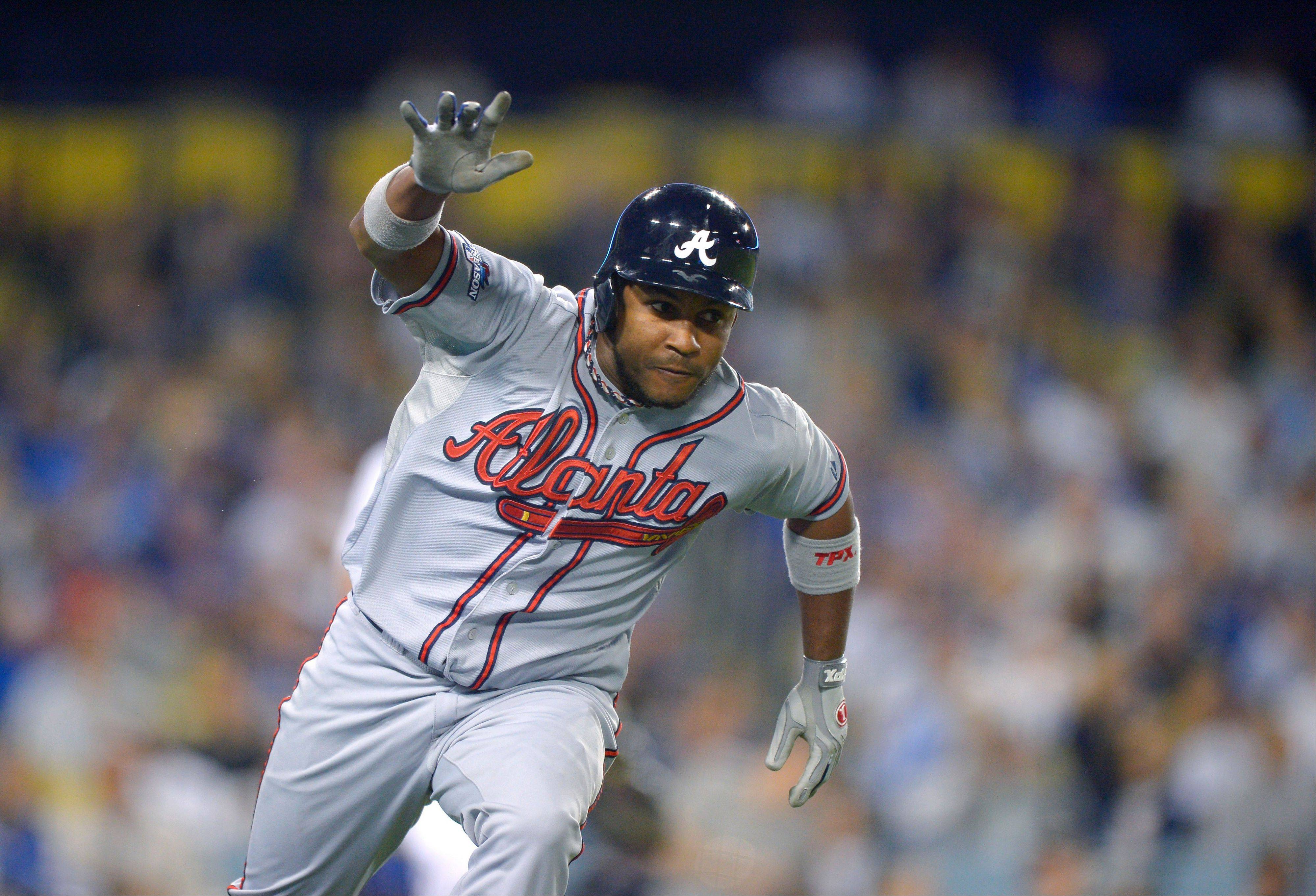 The Braves' Jose Constanza runs to first after hitting a single to score Elliot Johnson in the seventh inning of Game 4 Monday night in Los Angeles.