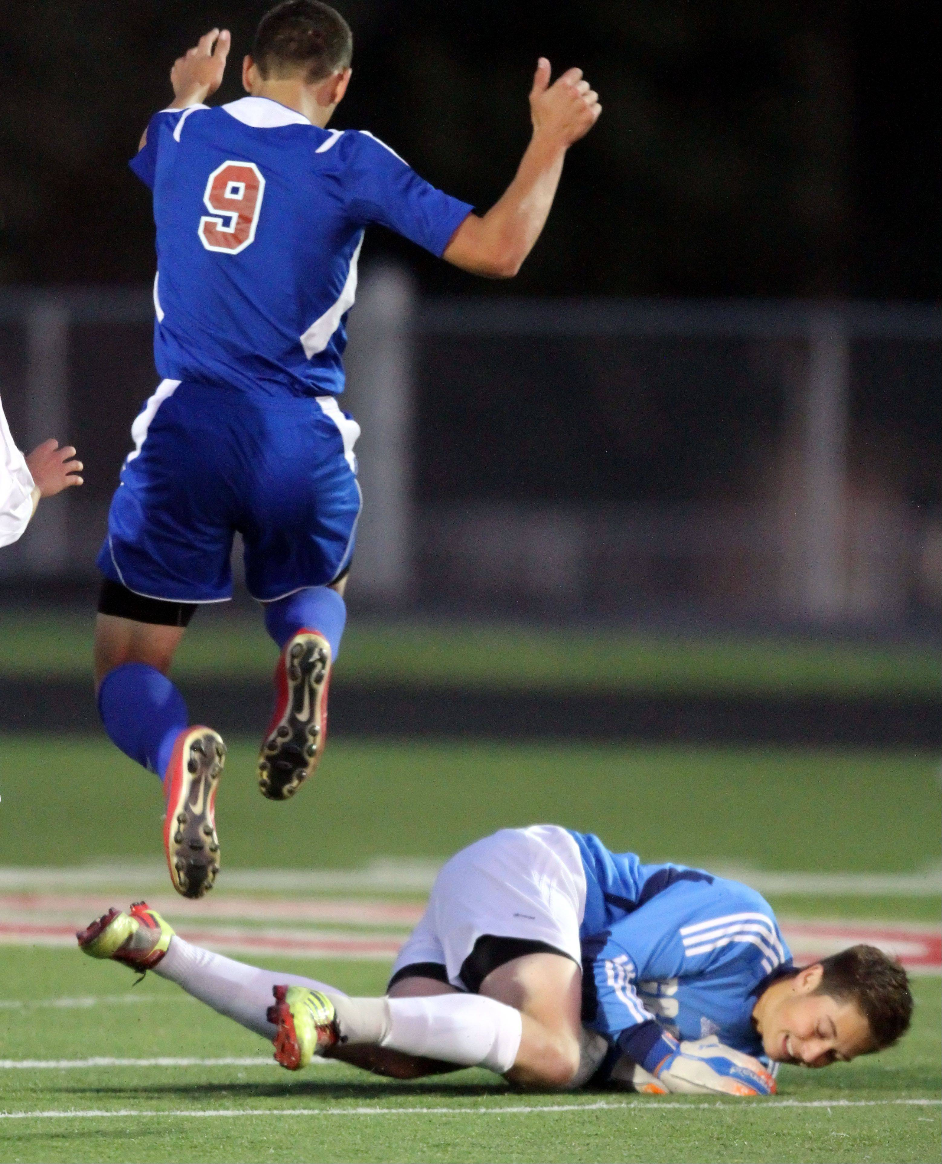 Lakes' Richard Galat, left, leaps as Grant goalie Nick Heidenthal makes a save Monday night at Grant.