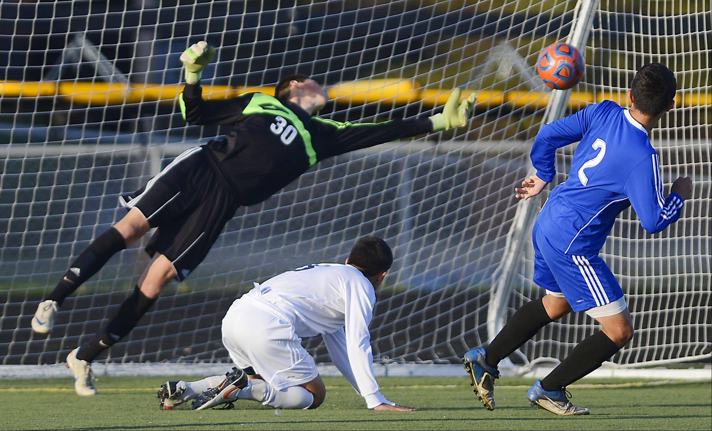 Streamwood goalkeeper Sergio Blanco reaches to block a shot by Larkin's Moises Raya Monday in Streamwood.