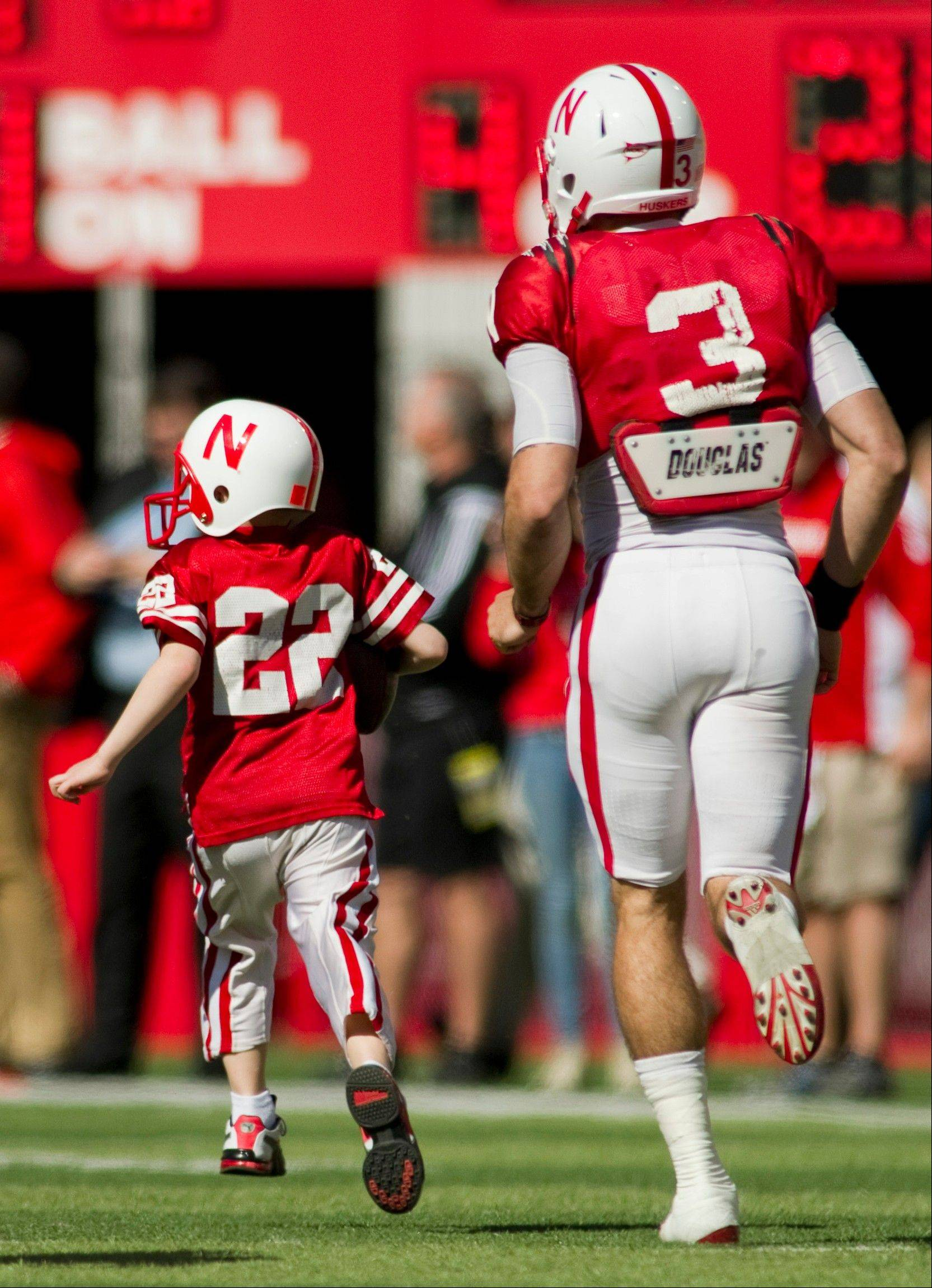 Nebraska's Taylor Martinez (3) guides Jack Hoffman of Atkinson, Neb., down the field for his touchdown play during a special segment dedicated to Jack at the Red-White spring game at Memorial Stadium in Lincoln, Neb.