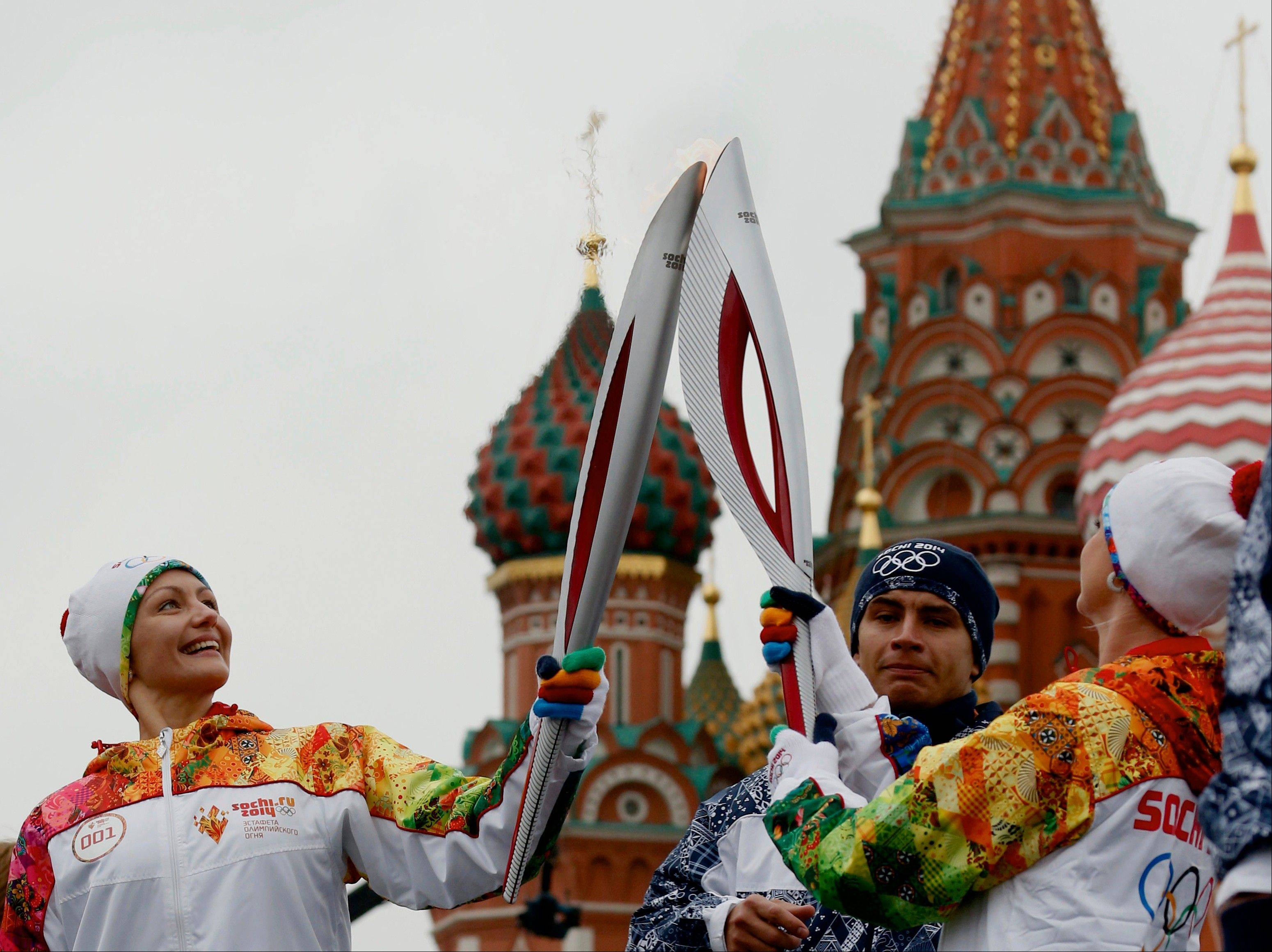 Russian Olympic gold medalists Anastasya Davydova, a synchronized swimmer, left, and Svetlana Khorkina, a gymnast, join their torches during Monday's relay of the Olympic flame in Moscow. The St. Basil's Cathedral is seen in the background.